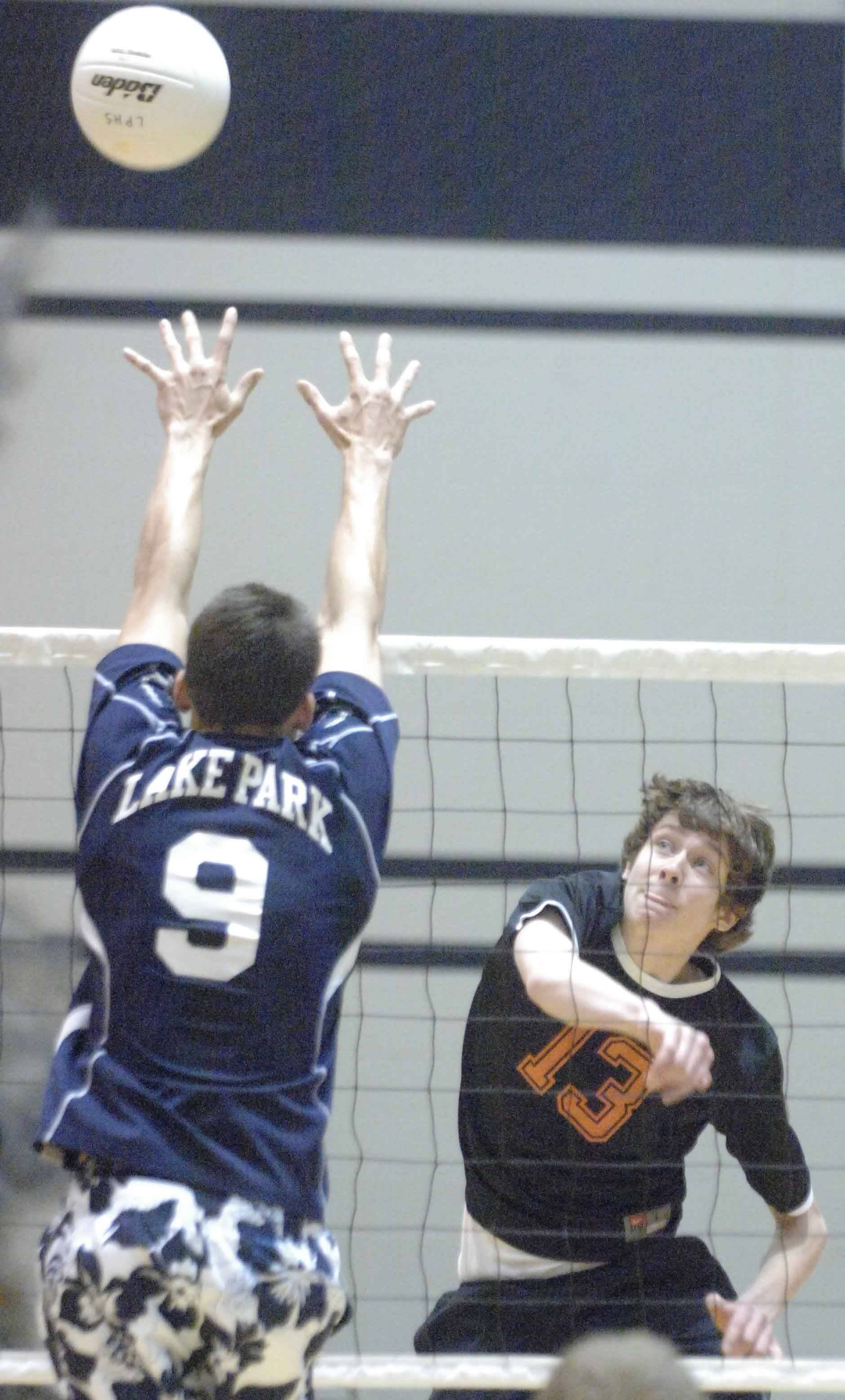 Trace Szczygiel,left, of Lake Park tries to block a shot from Tom Sheehan of St. Charles East. This took place during the St. Charles East at Lake Park boys volleyball game Tuesday.