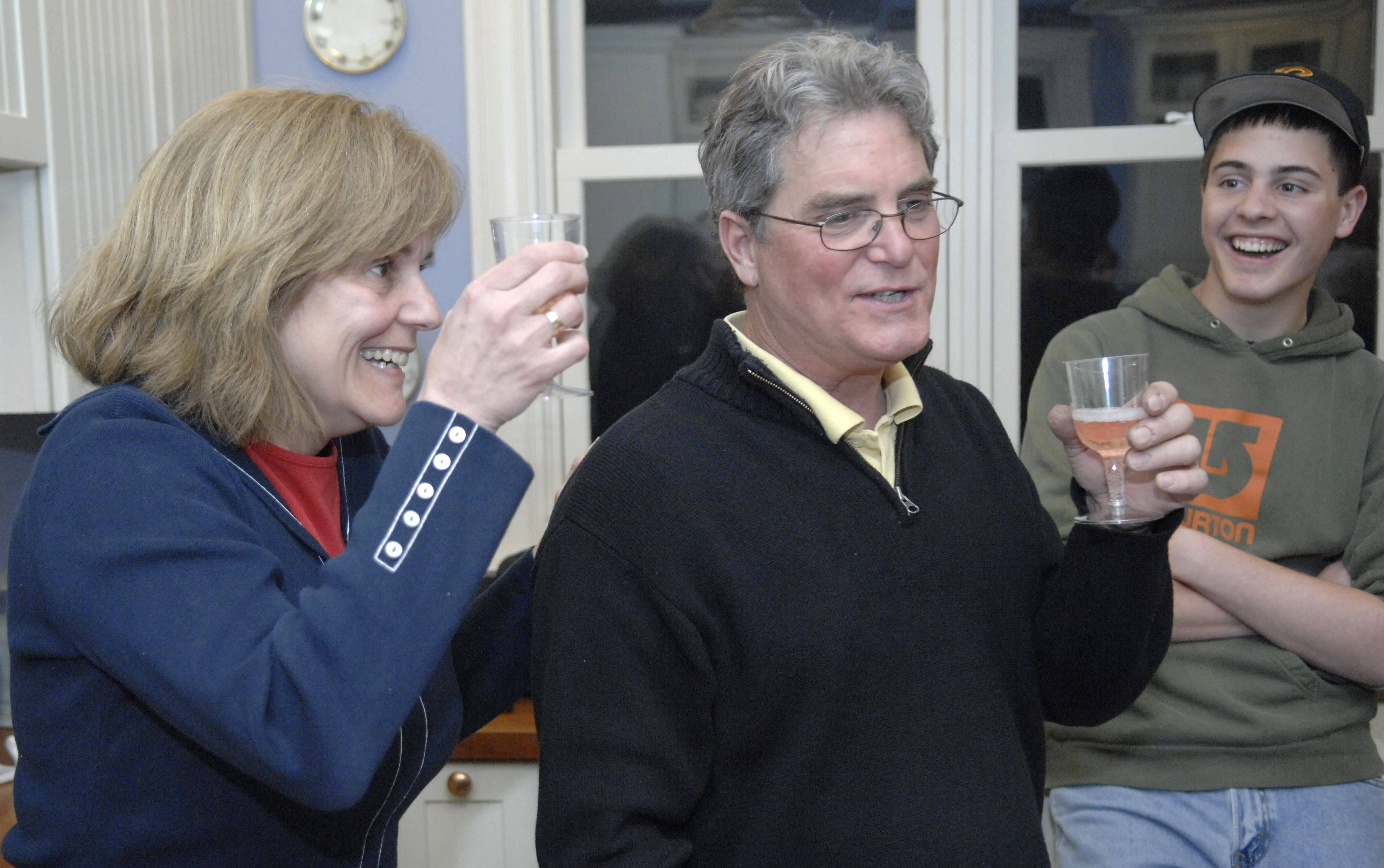 Batavia 4th Ward alderman candidate Susan Stark and husband Vincent Gatto toast with champagne in their Batavia kitchen as election results come in Tuesday night. They're joined by their son Jonathan Seagren.