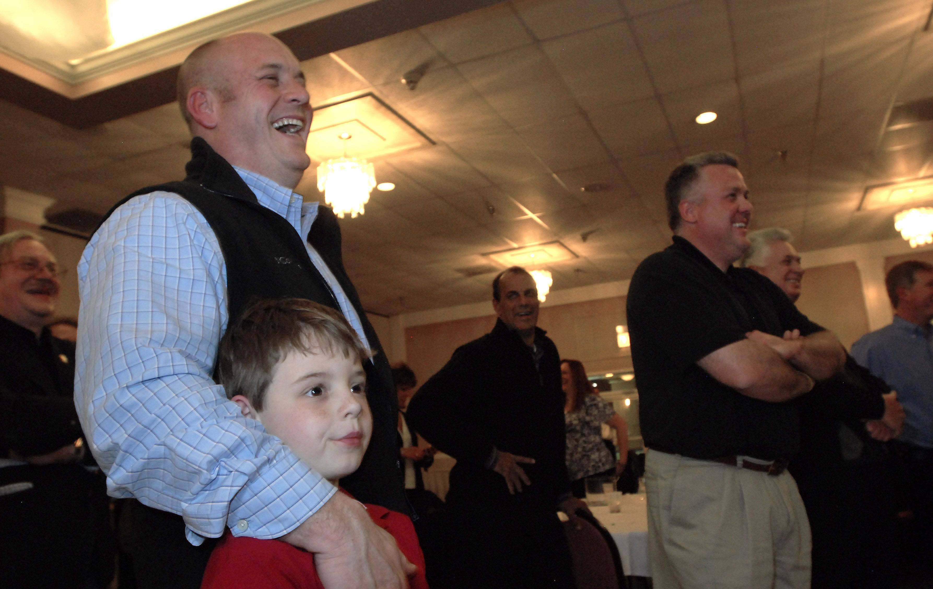 Robert Scott Williamson, with his son Jake, 7, laughs Nick Helmer's victory speech tonight.
