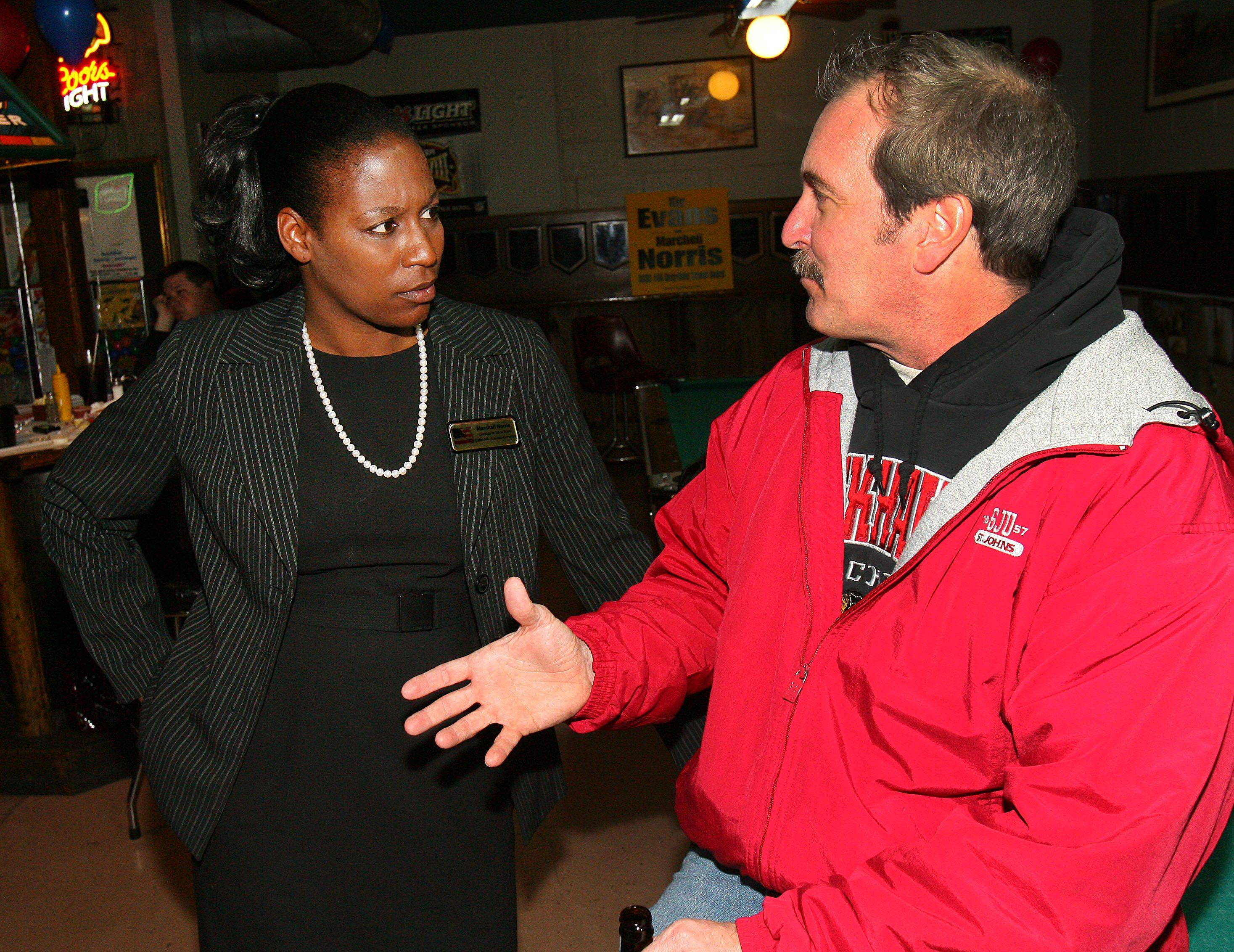 Grayslake District 46 school board candidate Marchell Norris, left, talks with Avon Township Trustee Chris Ditton Tuesday night at Last Chance Saloon in Grayslake.