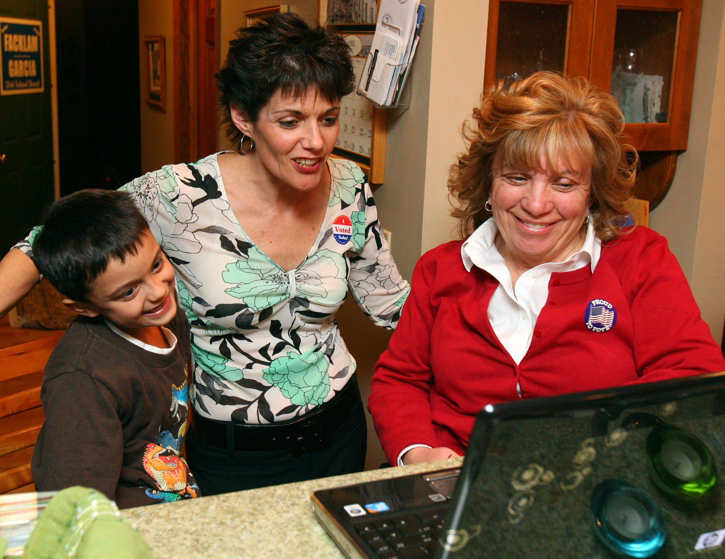 Grayslake District 46 school board incumbents Mary Garcia, left, and Susan Facklam look over election results with 8-year-old Mitchell Garcia at Facklam's Grayslake home Tuesday.