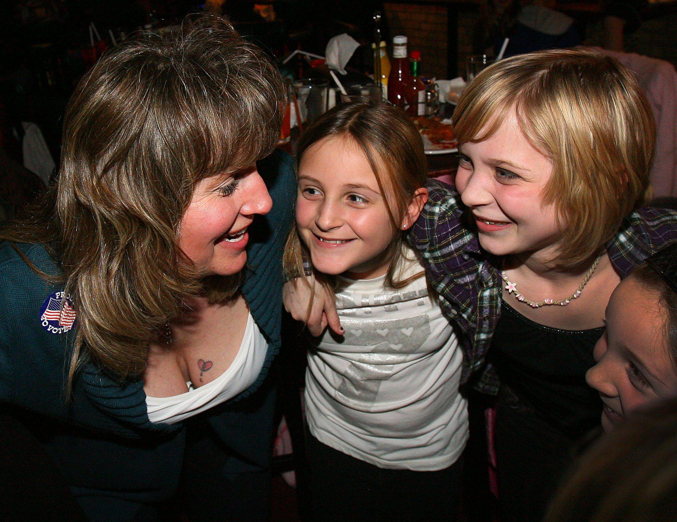 Shannon Smigielski, left, celebrates with her daughter, Morgan, 10, middle, and friend, Kelly Yoder, 10, after winning a seat on the Grayslake District 46 school board.