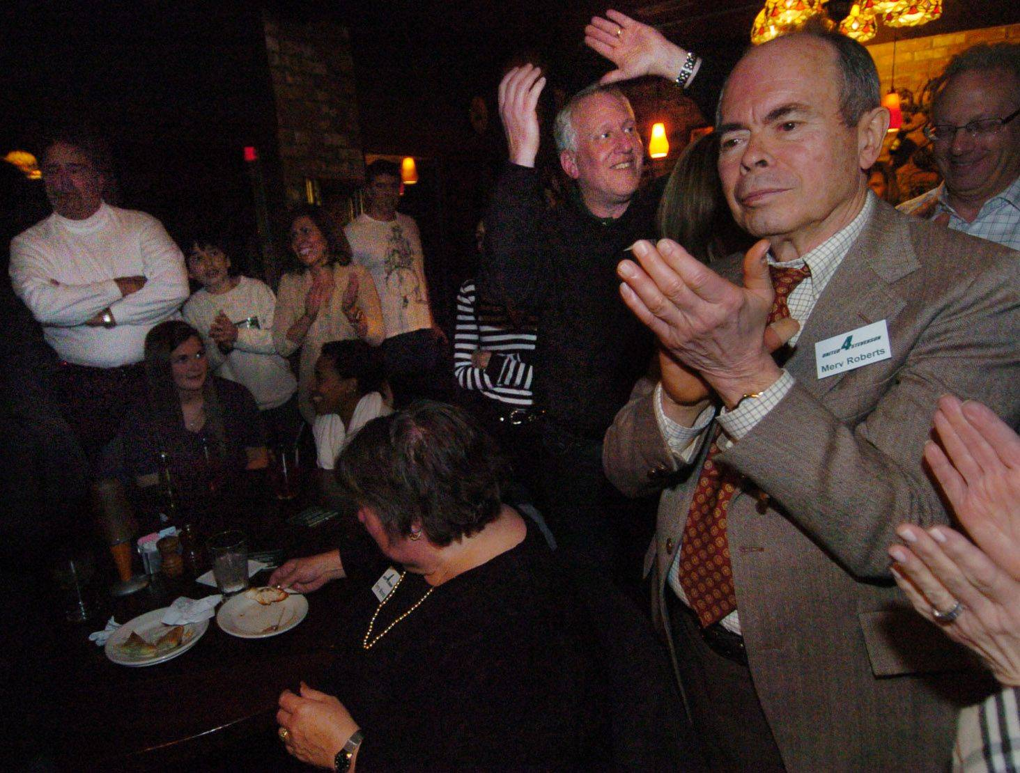 Merv Roberts, right, Bruce Lubin, with arms in the air, along with Terry Moons, seated, and David Weisberg, far left, celebrate during Stevenson High School District 125 victory party.