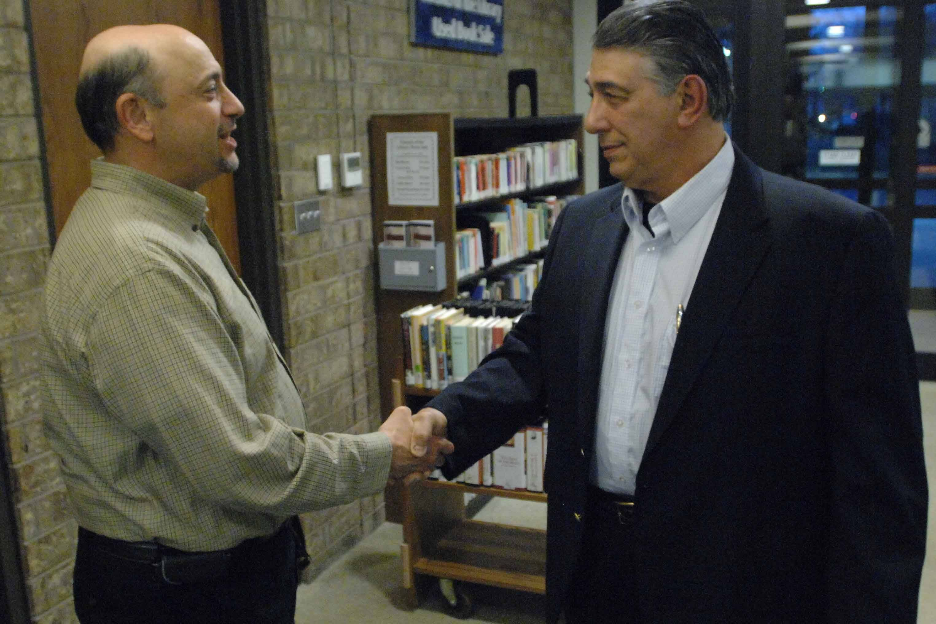 David DeRango, left, and Dominick Jeffrey shake hands before entering the Carol Stream Library's human resources meeting Wednesday.