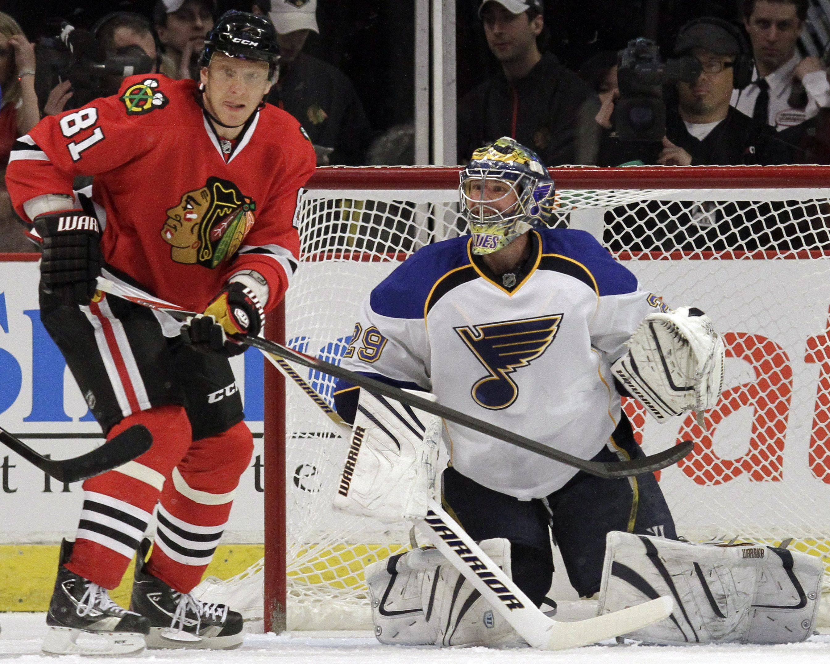 St. Louis Blues goalie Ty Conklin, right, and Chicago Blackhawks' Marian Hossa watch the puck during the first period of an NHL hockey game in Chicago, Wednesday, April 6, 2011.