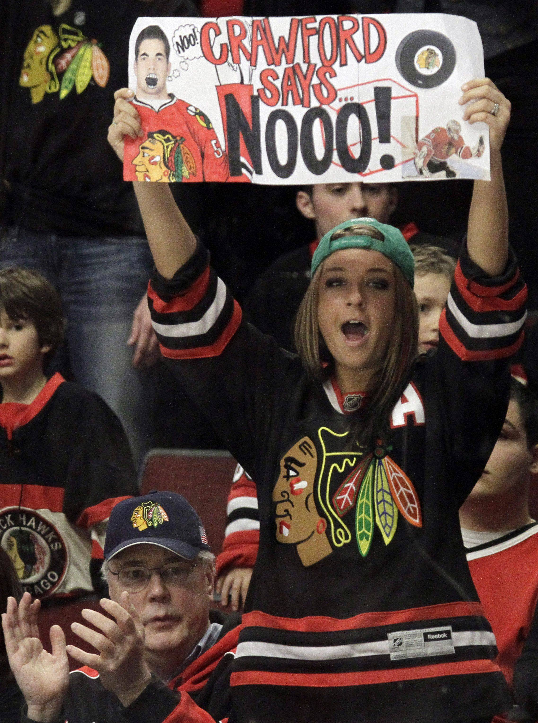 A Blackhawks fan holds a sign during the overtime period of an NHL hockey game against the St. Louis Blues in Chicago on Wednesday. The Blackhawks won 4-3 in overtime, and Patrick Sharp returned to the lineup after missing more than two weeks with a knee injury.