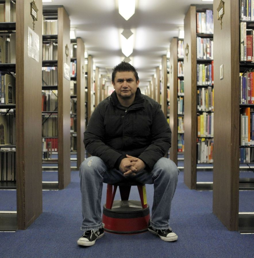 Fernando Molina sits for a portrait at the main library in downtown Aurora.