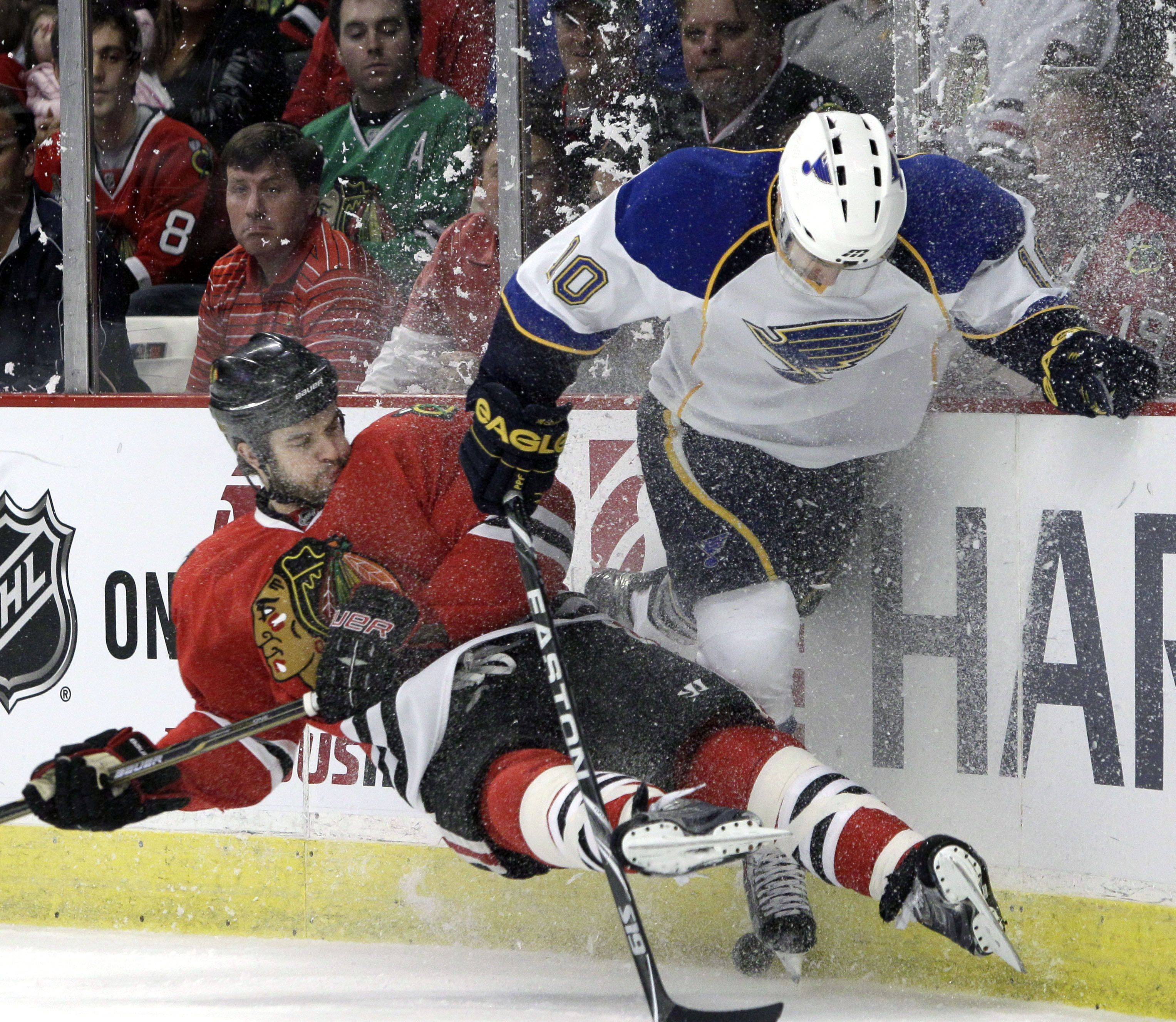 St. Louis Blues' Andy McDonald, right, battles Chicago Blackhawks' Brent Seabrook for the puck during the first period of an NHL hockey game in Chicago, Wednesday, April 6, 2011.