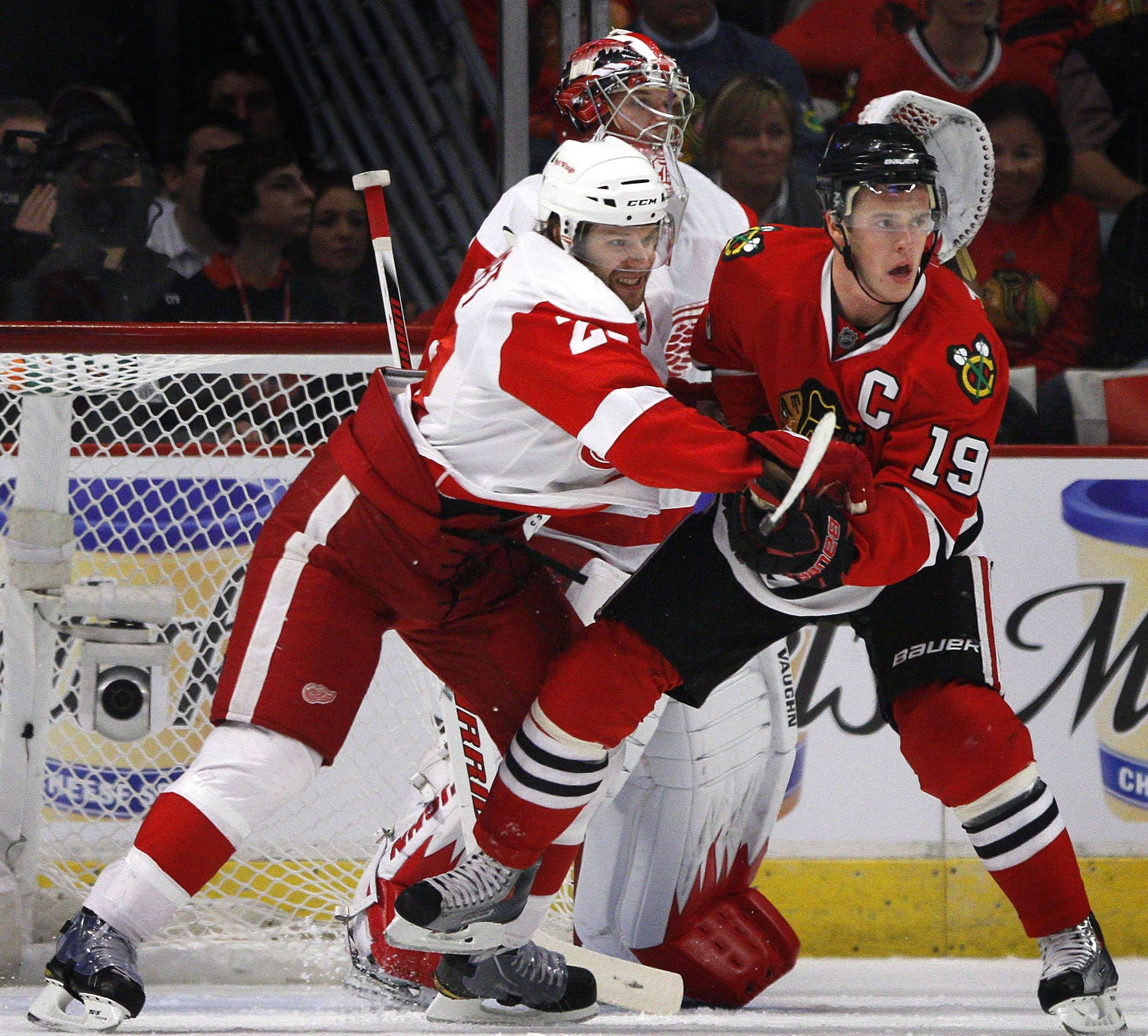 The Red Wings' Brad Stuart, left, tries to keep the Blackhawks' Jonathan Toews, right, from planting in front of Red Wings goalie goalie Jimmy Howard, center, during the first period of an NHL hockey game on Sunday, April 10, 2011.