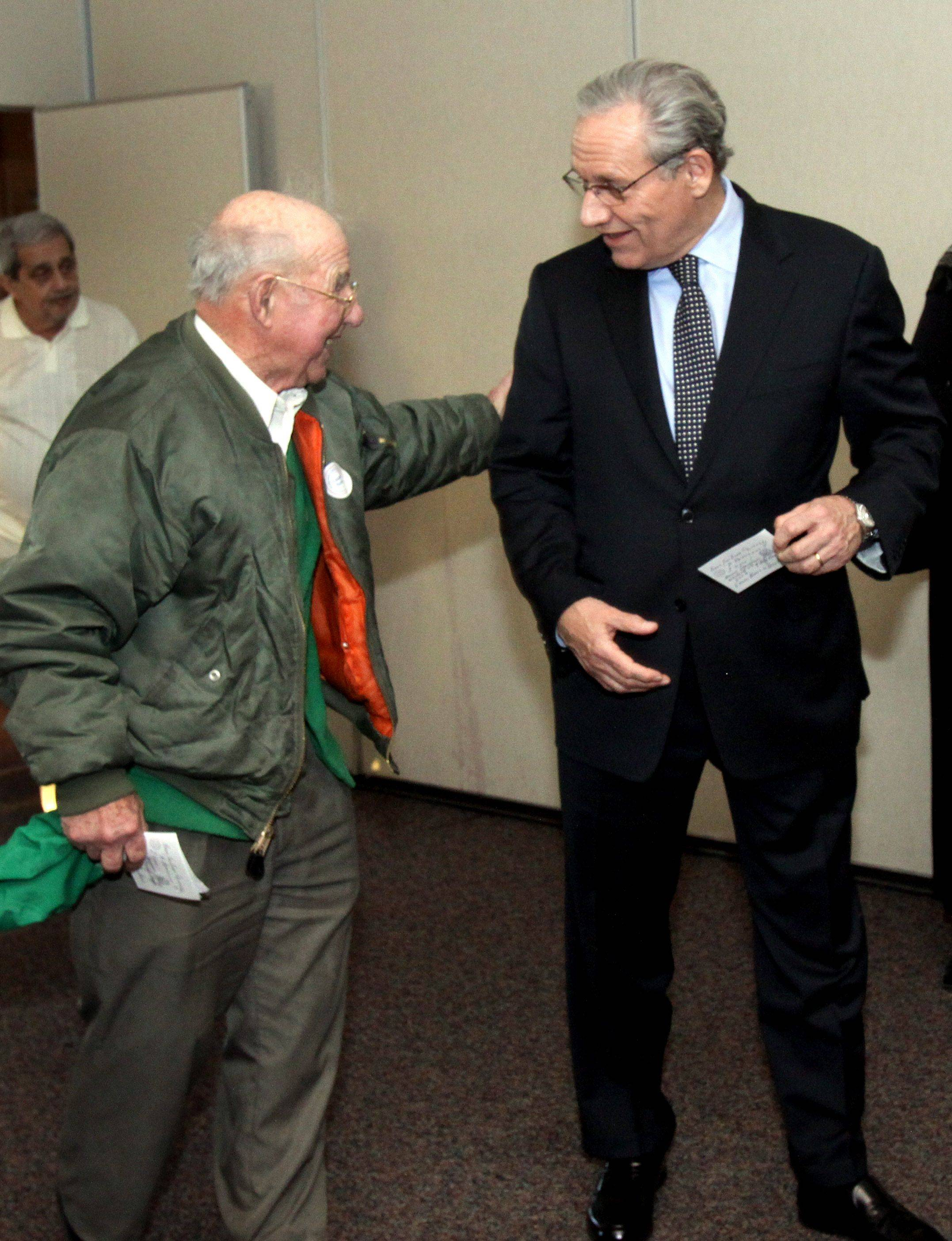 Bernie Hurley, left, of Wheaton says hello to his former physical education student, Bob Woodward, before Tuesday's event at Benedictine University in Lisle.