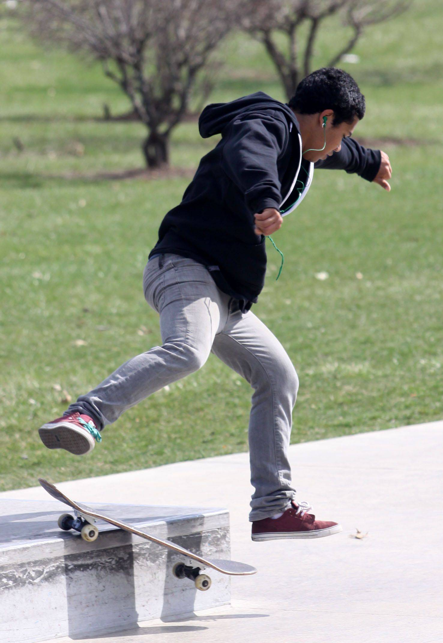 Ivan Arline, 17, of West Dundee performs a trick on a cement and steel rail at the skate area of Huffman Park in West Dundee.