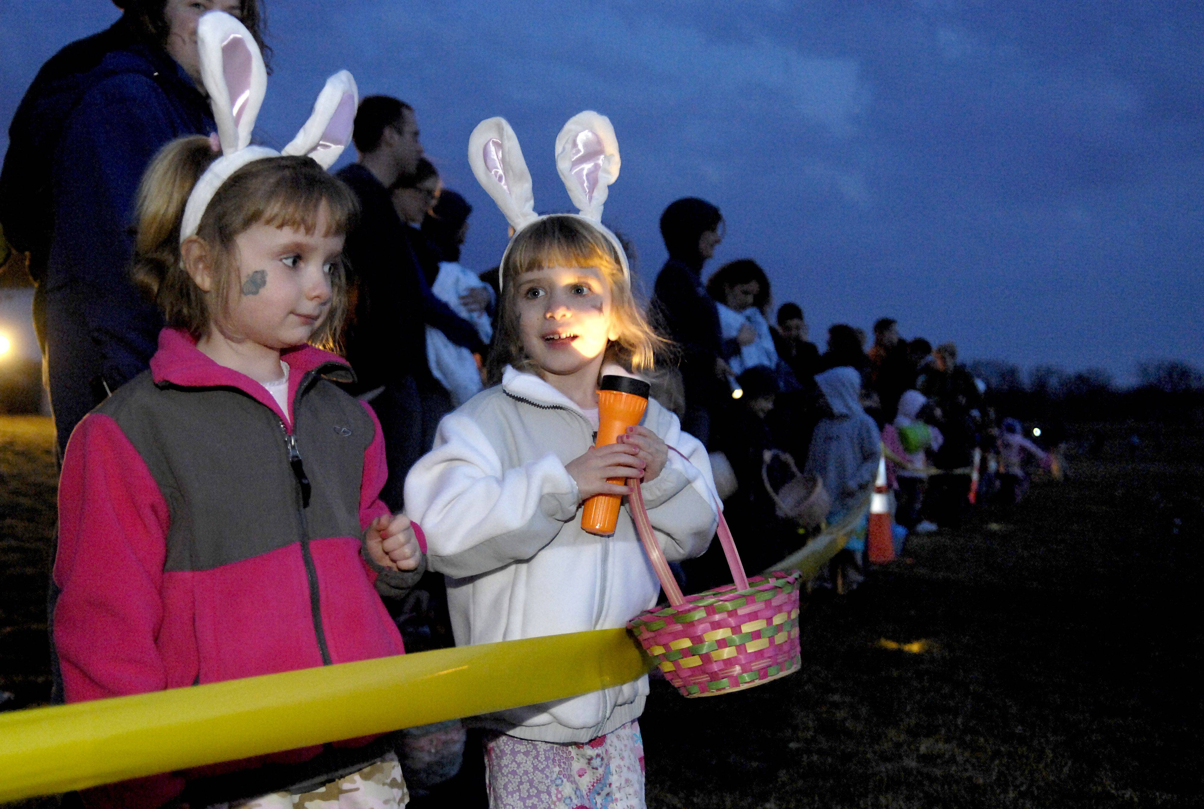 Laura Stoecker/lstoecker@dailyherald.com ¬ Easter basket? Check. Bunny ears? Check. Flashlight?! Annika and Zoe Kippley, 4, twins from Batavia, wait anxiously for the Batavia Easter egg hunt by flashlight to start at Prairie Path Park on Friday, March 19. Kids aged 2-8 were let loose at 7:30 to hunt down their eggs.