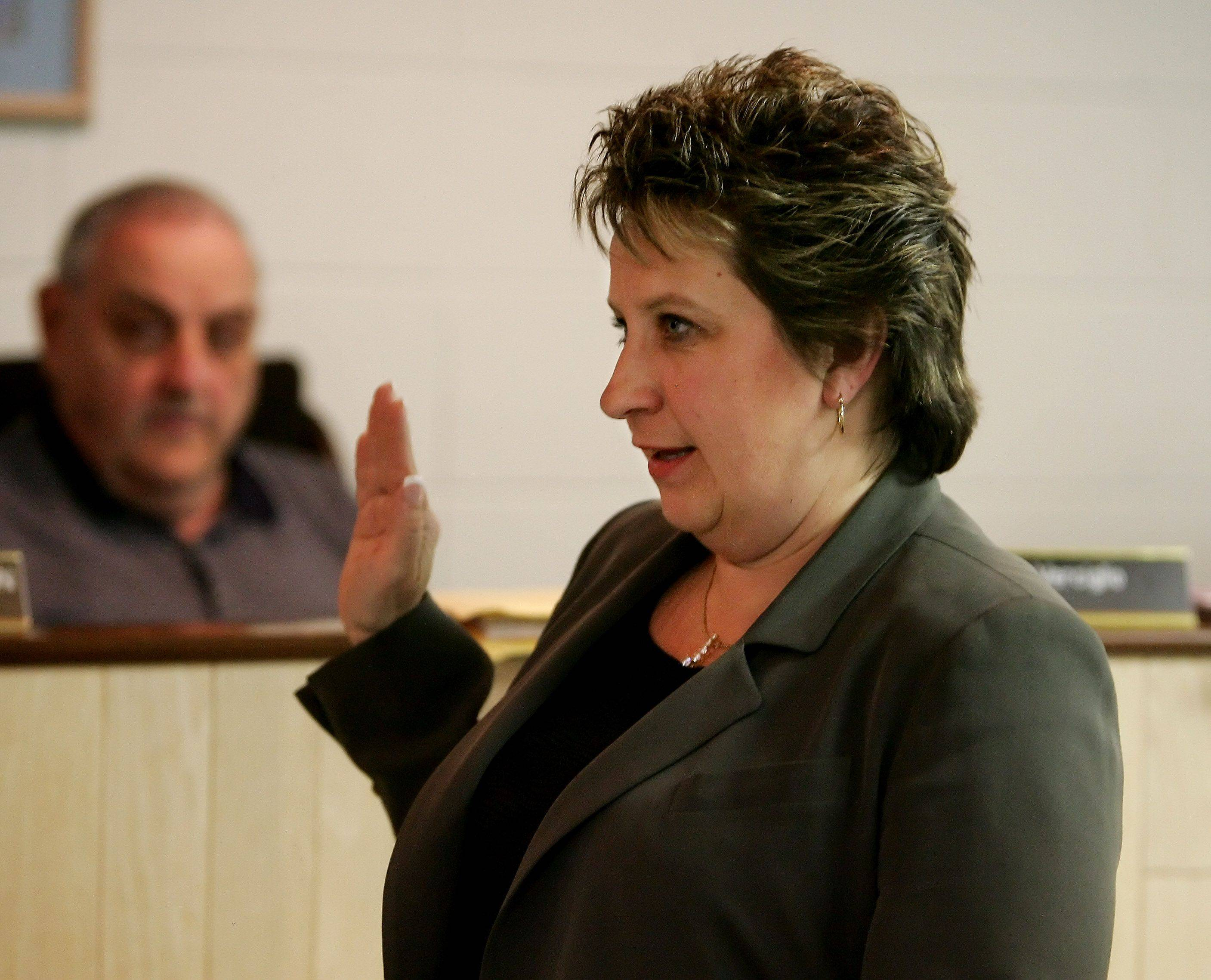 Island Lake Mayor Debbie Herrmann, shown here taking the oath of office in 2009, continues to face an assault on her powers by trustees who oppose her.