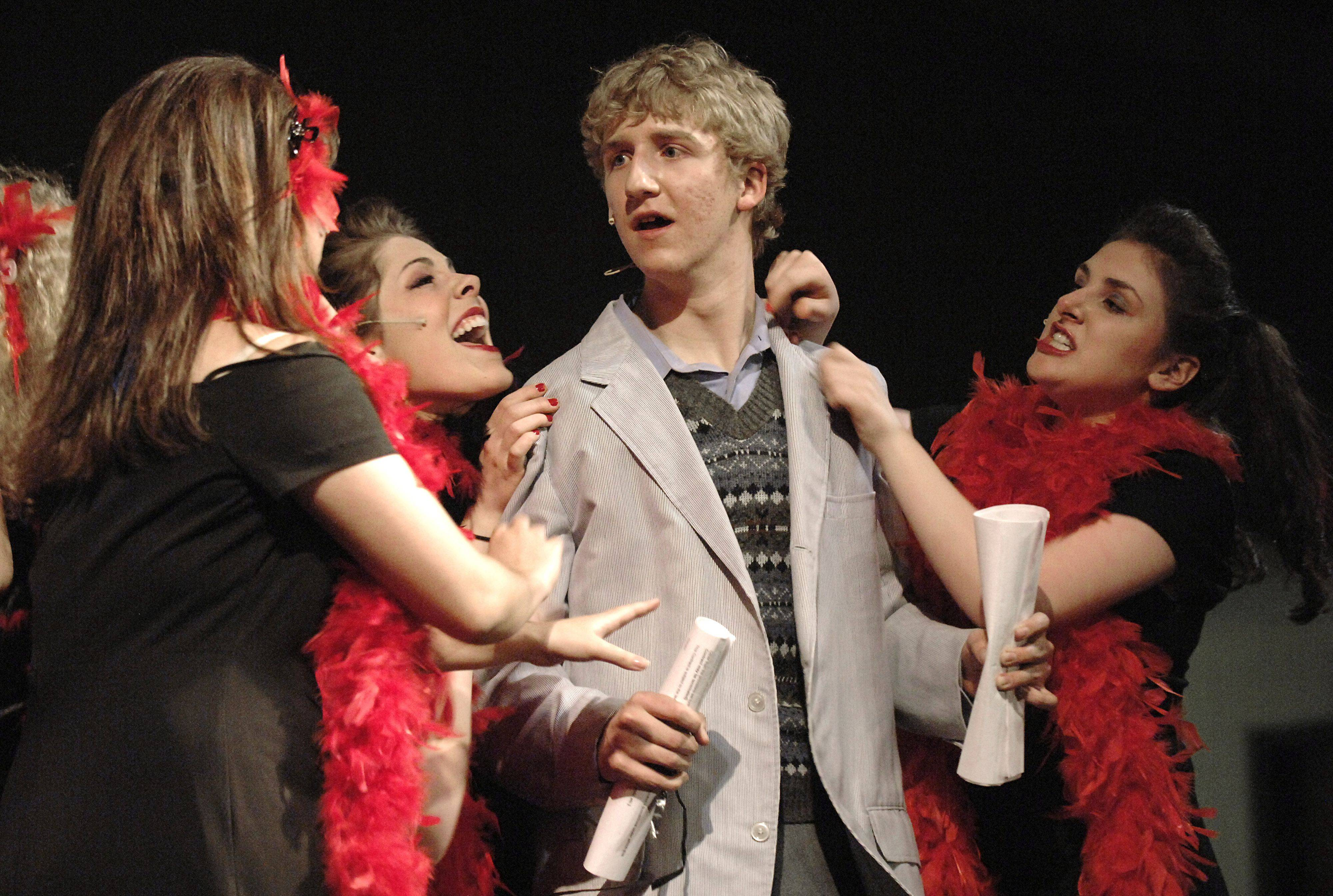 "Seymour, played by senior Doug Burrichter, is flanked by Doo-wop girls performing in Batavia High School's production of ""Little Shop of Horrors."""