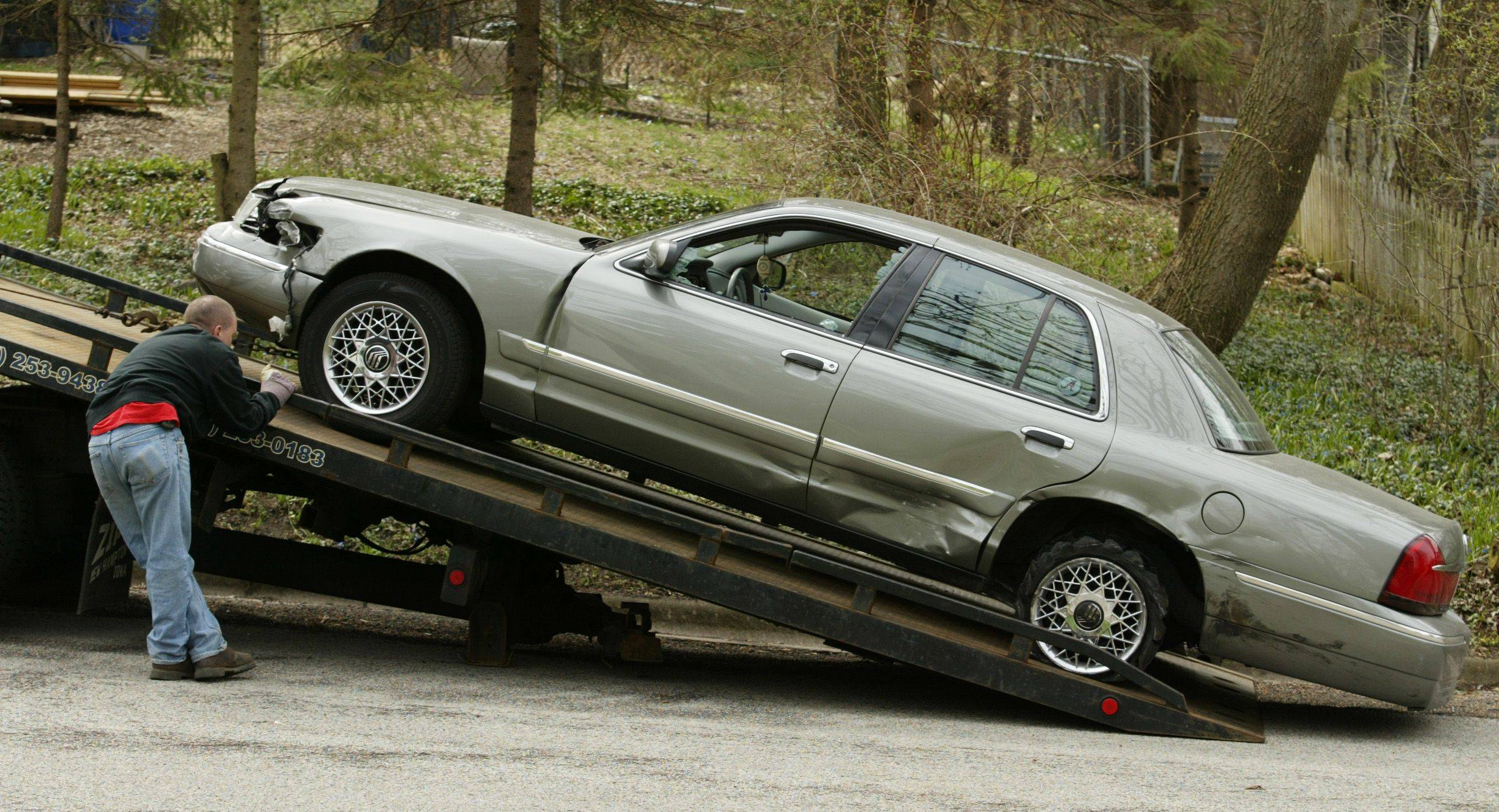 Sean Dourlain of Hillside Towing brings a vehicle involved in a high-speed chase Thursday morning up on a flatbed truck after the driver's apprehension near downtown East Dundee. The driver, described by witnesses as a young man, was wanted as part of a death investigation in Arlington Heights.