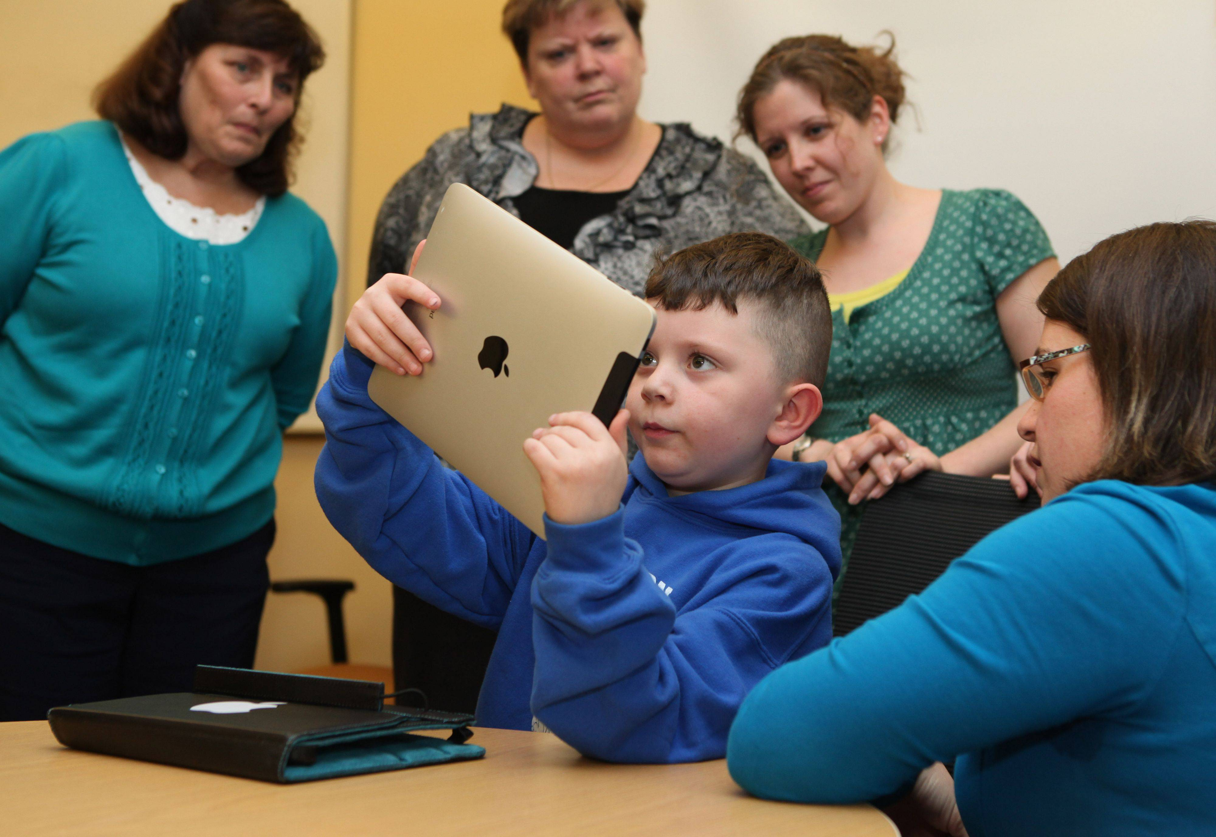Kindergartner Lucius Rice, 6, center, demonstrates to Kindergarten teachers Sue Larue, left to right, Kelly McCarthy and Amy Himerl, how to uses an iPad in Auburn, Maine. The teachers were given iPads to try out in preparation for next year when nearly 300 kindergartners will be given their own iPad2s.