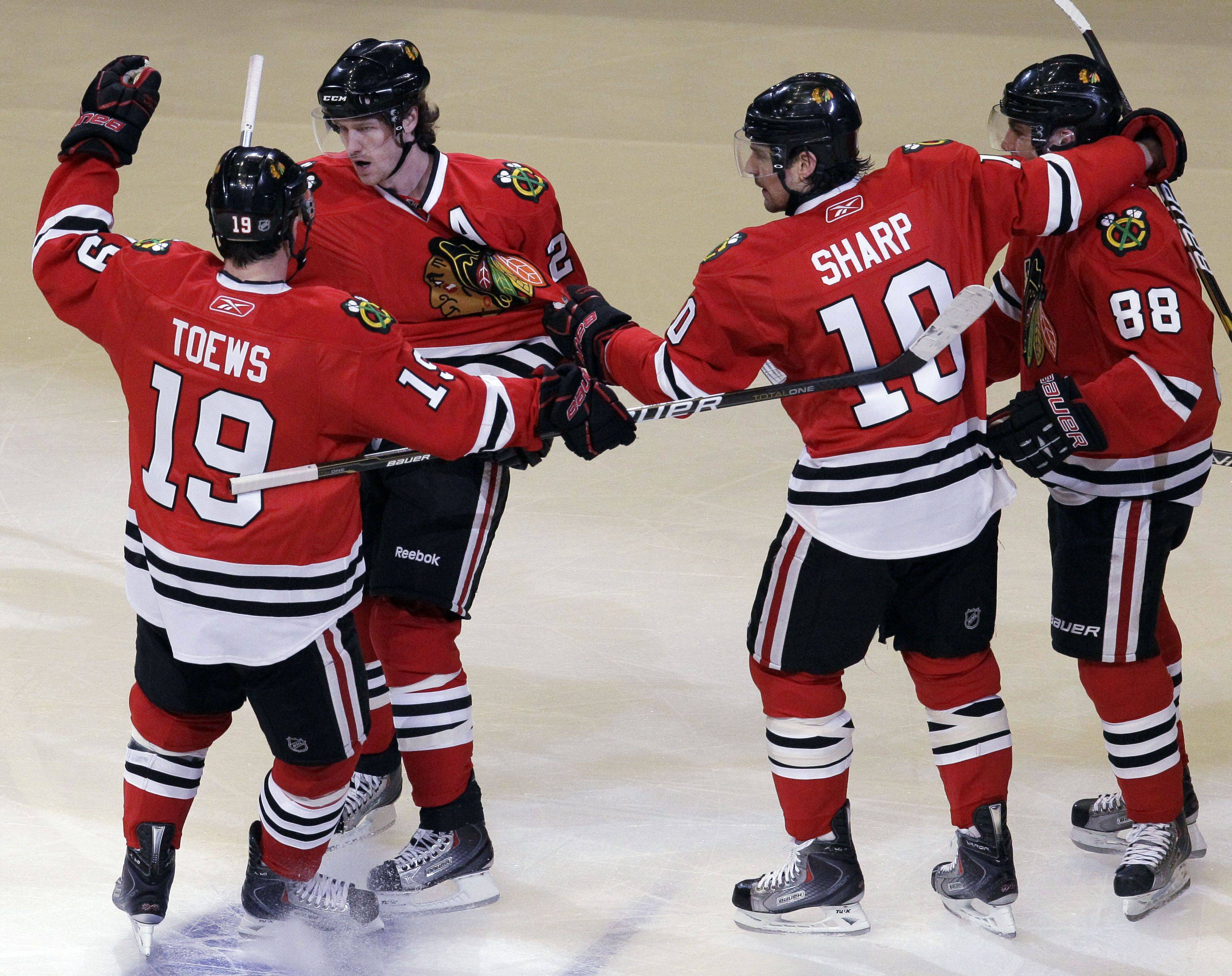 Blackhawks' Duncan Keith, second from left, celebrates with Jonathan Toews, left, Patrick Sharp (10) and Patrick Kane after scoring his goal during the first period of Game 3.