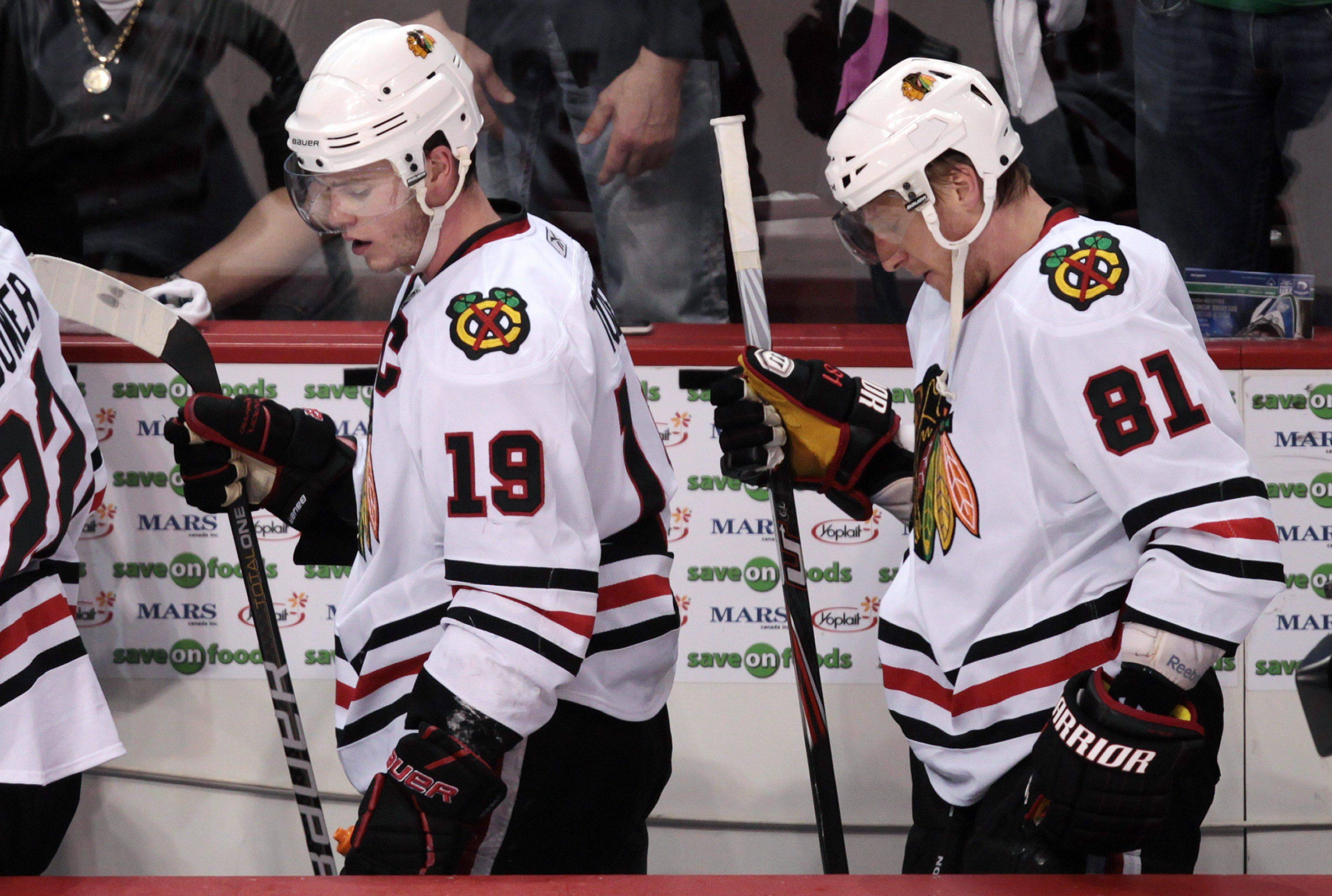 "Blackhawks forwards Jonathan Toews, left, and Marian Hossa leave the bench after losing to the Vancouver Canucks 4-3 in game 2 of their NHL Western Conference quarterfinal playoff series. Toews said the top players ""need to play better"" when they meet the Canucks tonight at the United Center."