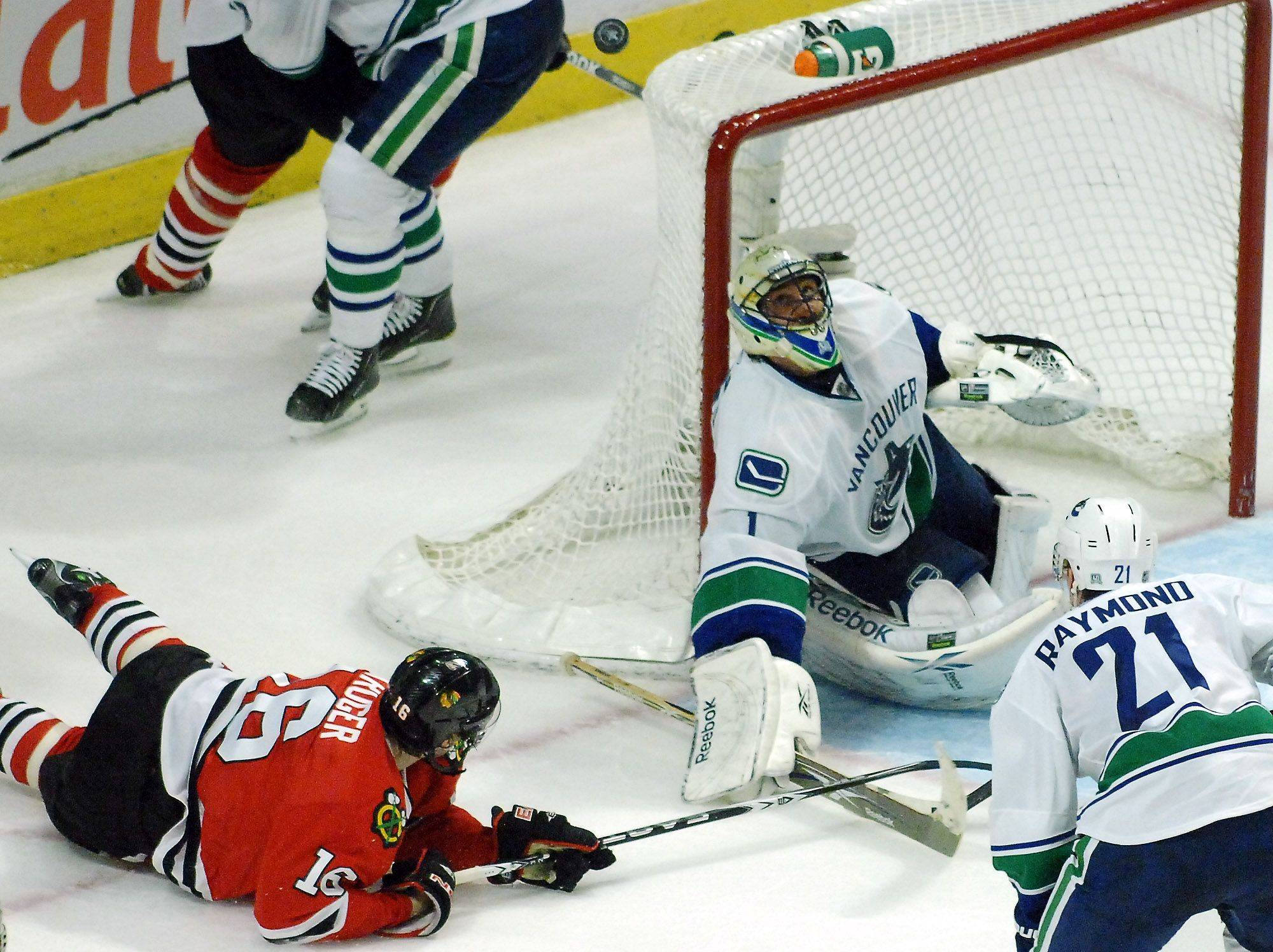 Vancouver Canucks goalie Roberto Luongo blocks a shot by Chicago Blackhawks center Marcus Kruger.