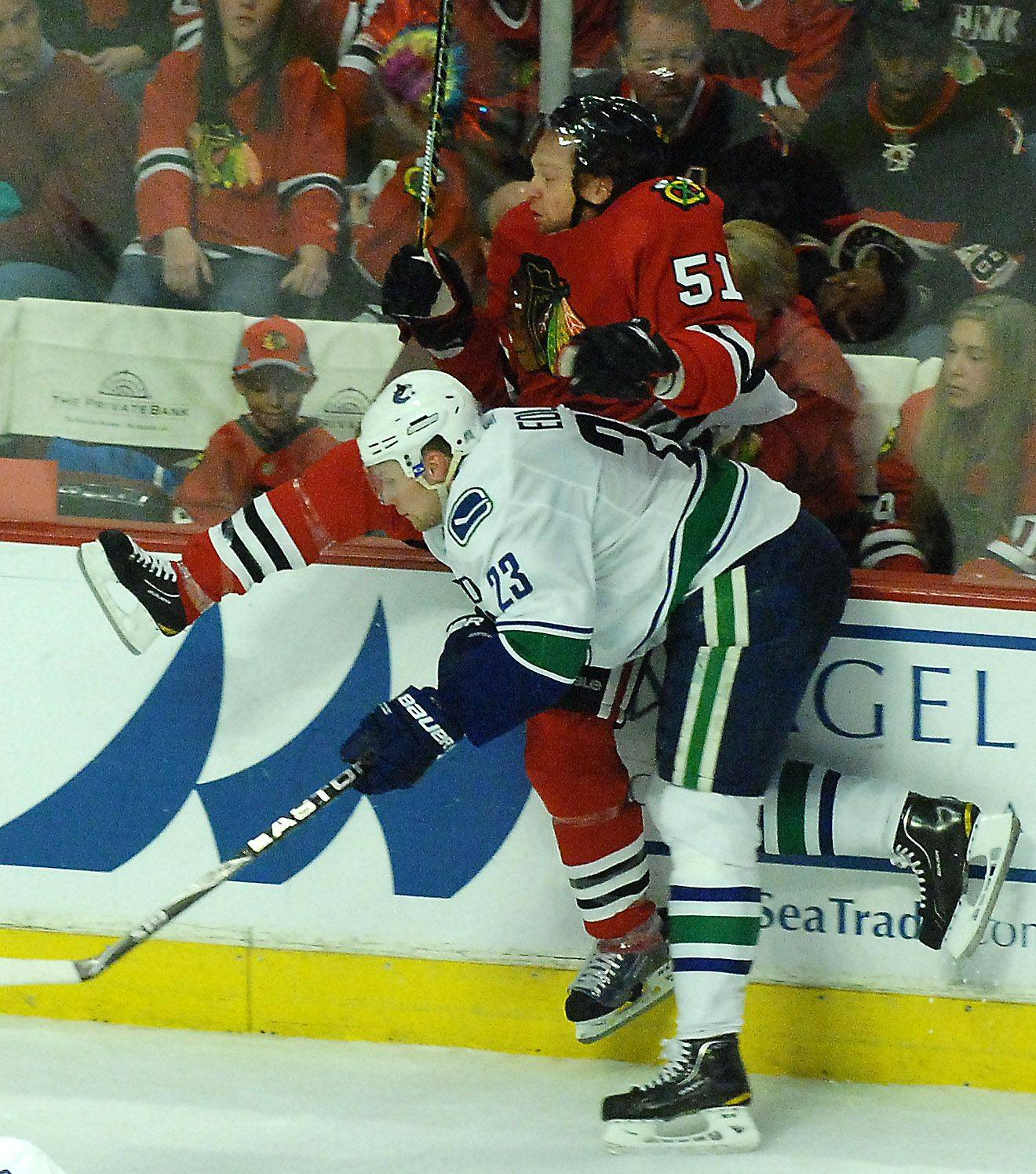 Chicago Blackhawks defenseman Brian Campbell is put into the boards by Vancouver Canucks defenseman Alexander Edler.