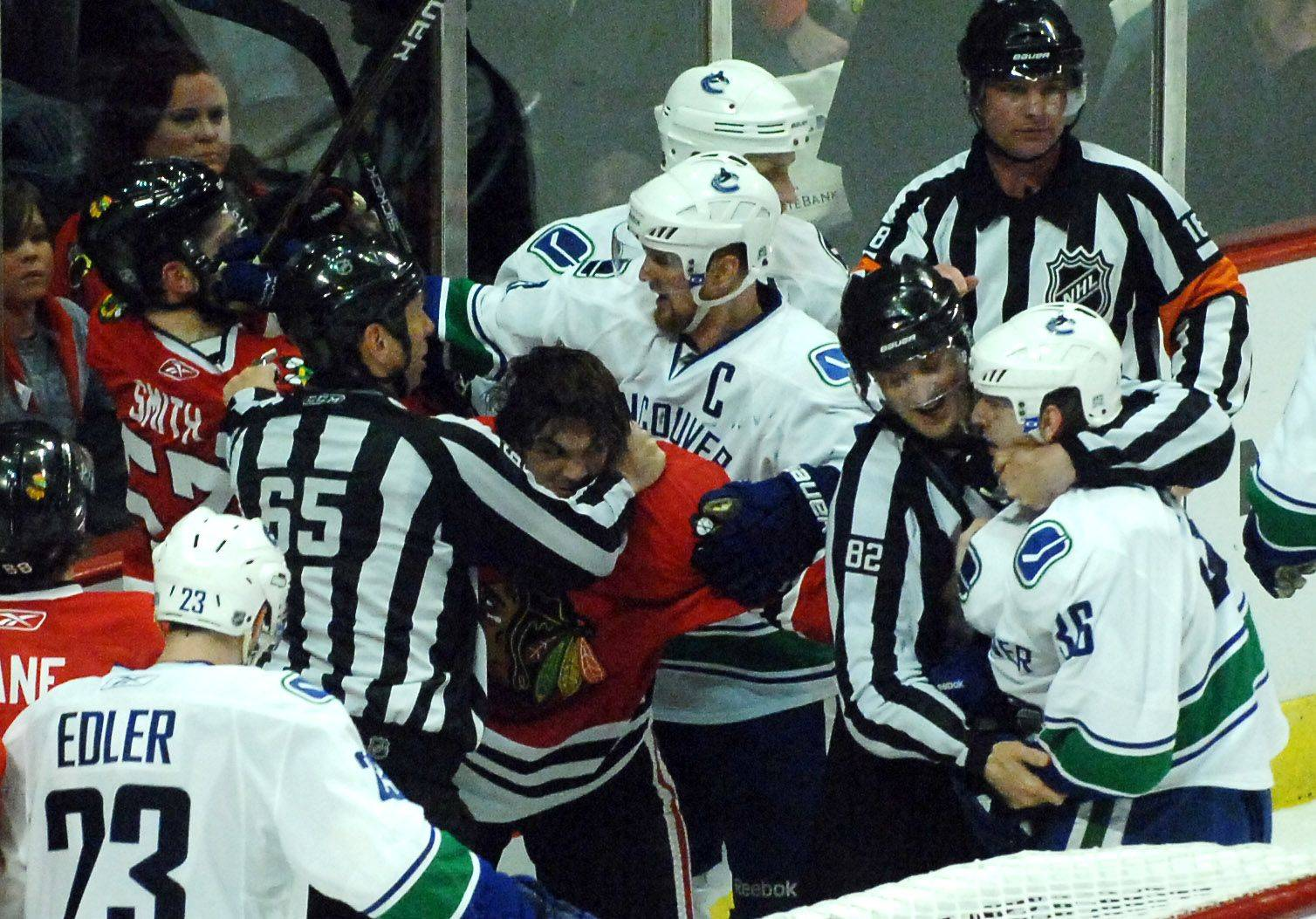 Chicago Blackhawks center Michael Frolik (67) and Vancouver Canucks right wing Jannik Hansen (36) are separated by the officials as the final seconds tick off the clock.