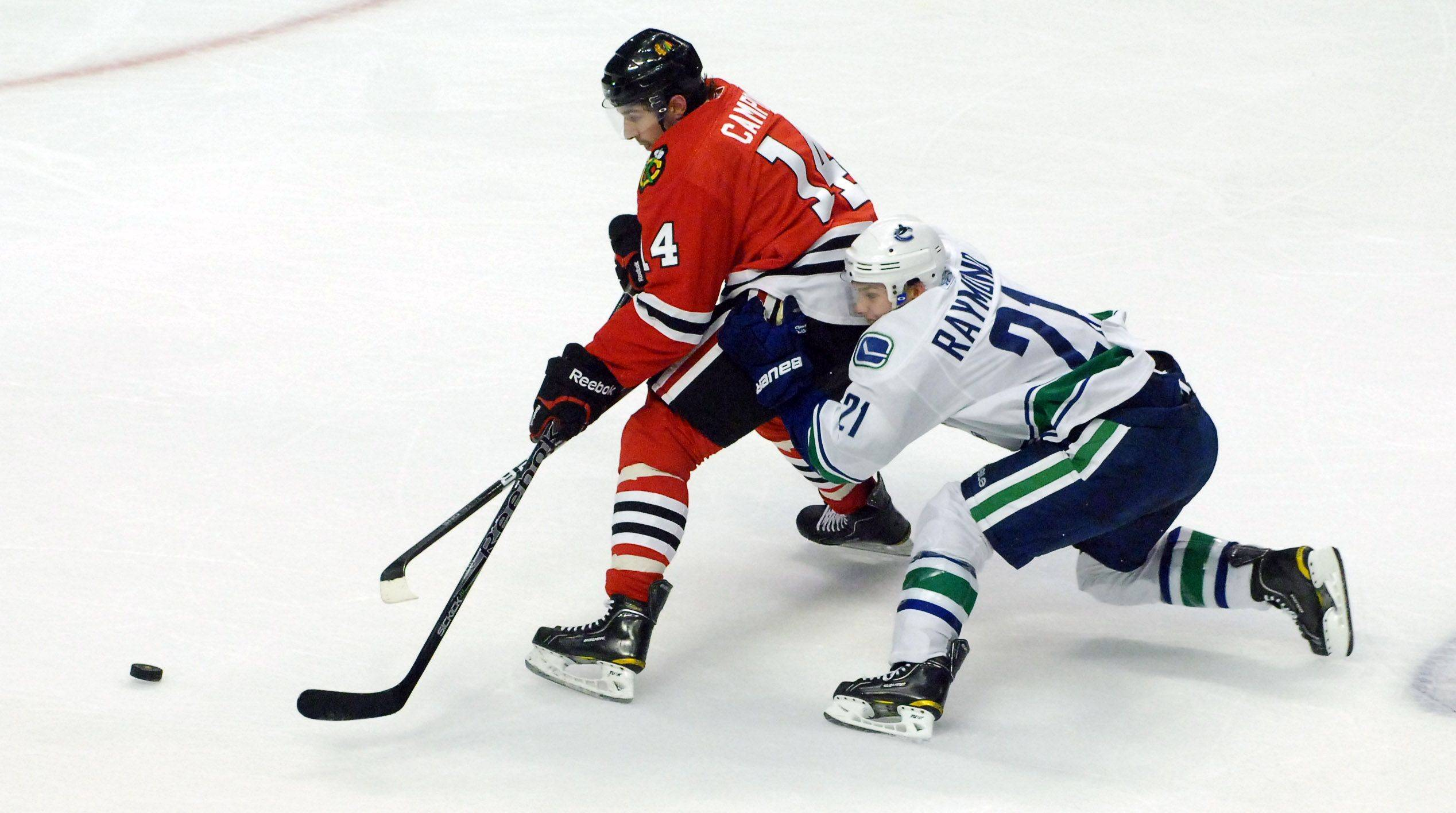Chicago Blackhawks defenseman Chris Campoli battles for the puck with Vancouver Canucks left wing Mason Raymond.