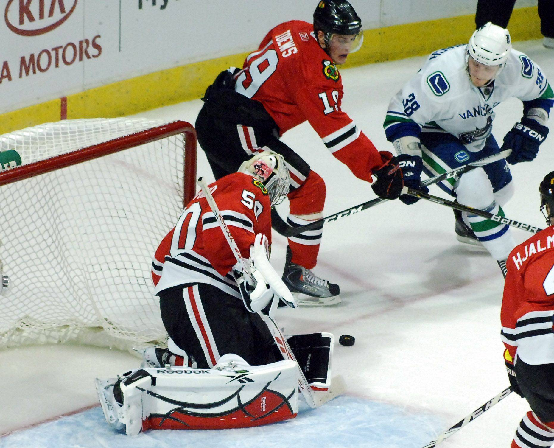 Chicago Blackhawks goalie Corey Crawford turns away a shot by Vancouver Canucks right wing Victor Oreskovich.
