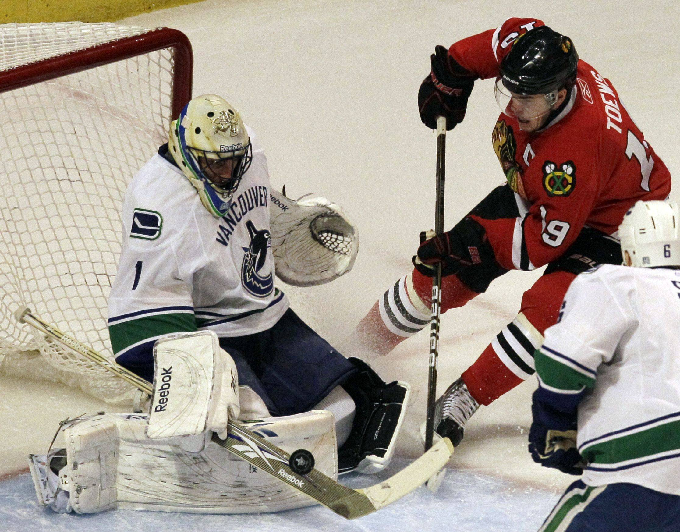 Vancouver Canucks goalie Roberto Luongo, left, blocks a shot by Chicago Blackhawks center Jonathan Toews during the first period of Game 3 of an NHL hockey Stanley Cup playoff series Chicago, Sunday.