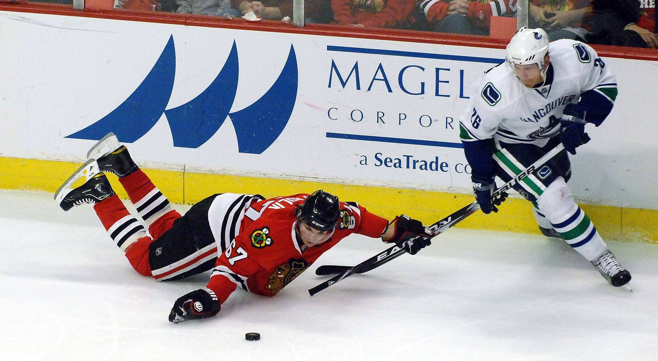 Chicago Blackhawks center Michael Frolik goes down battling Vancouver Canucks right wing Mikael Samuelsson.