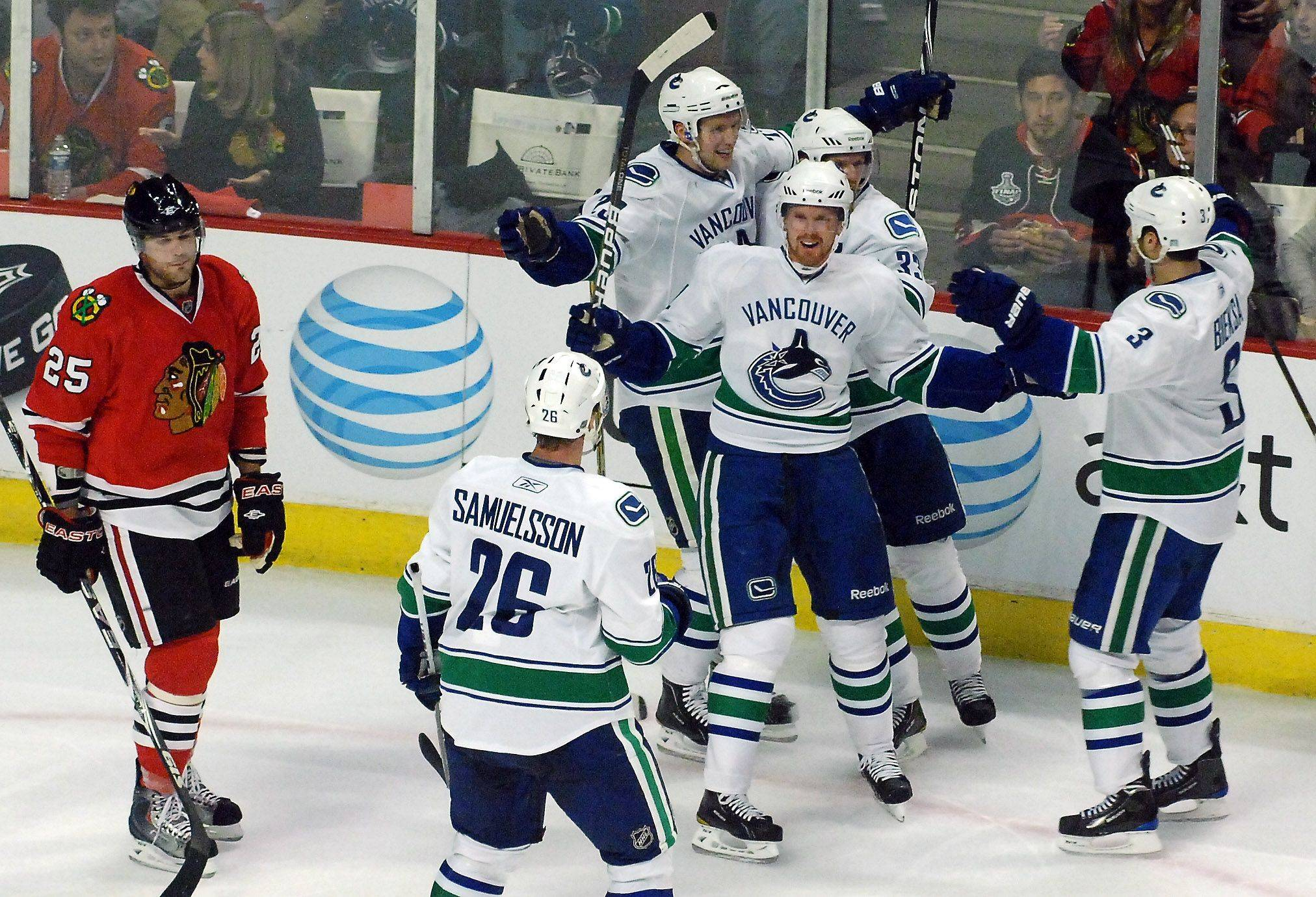 Vancouver Canucks left wing Daniel Sedin (22) and his teammates celebrate his second period goal near Chicago Blackhawks left wing Viktor Stalberg.