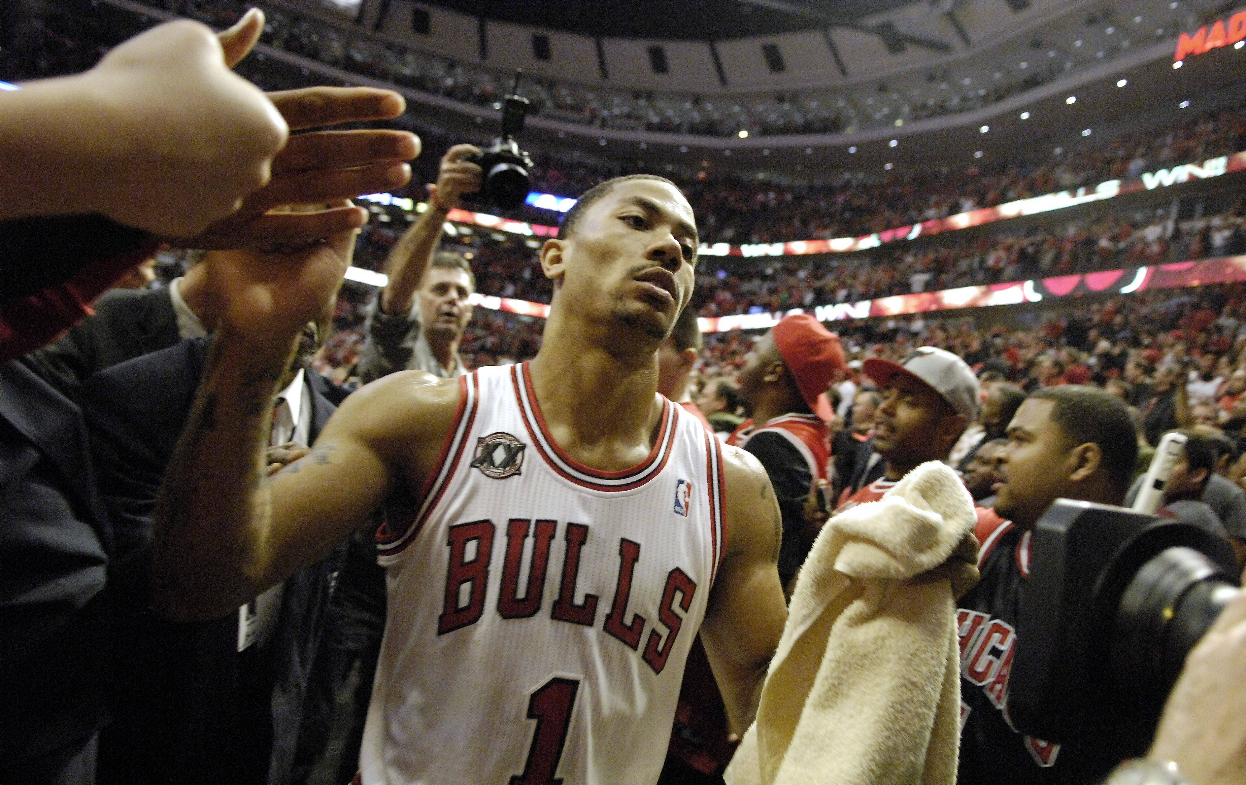 Chicago Bulls point guard Derrick Rose (1) high-fives the fans as he leaves the court after Game One of the NBA Eastern Conference Quarterfinals Saturday at the United Center in Chicago.