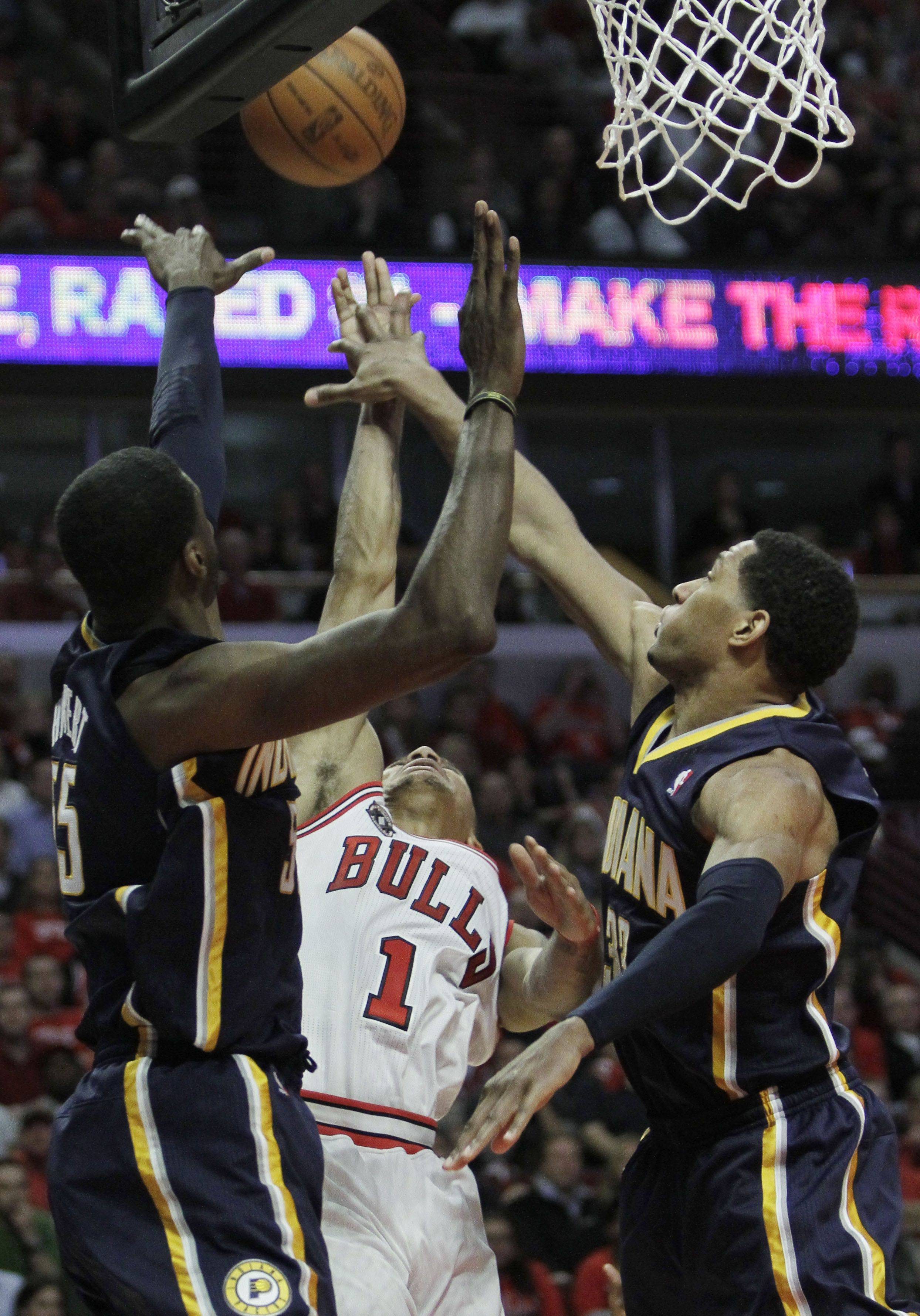 Chicago Bulls' Derrick Rose, center, shoots over Indiana Pacers' Roy Hibbert, left, and Danny Granger during the fourth quarter in Game 2 of a first-round NBA playoff basketball series Monday in Chicago. The Bulls won 96-90.