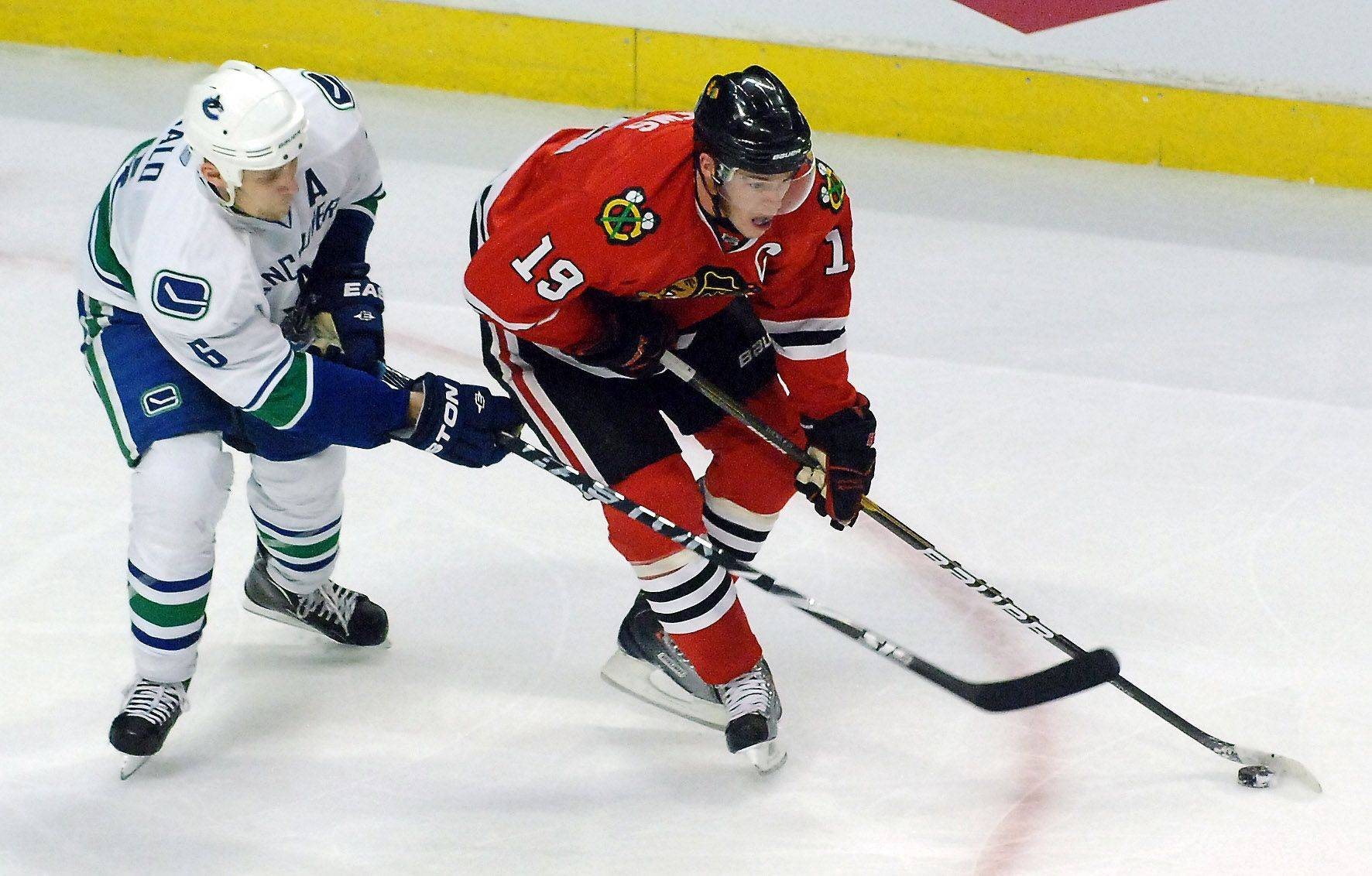 Chicago Blackhawks center Jonathan Toews (19) tries to find some room to skate past Vancouver Canucks defenseman Sami Salo (6) in the third period during Game Three of the NHL Western Conference Quarterfinals Sunday at the United Center in Chicago.