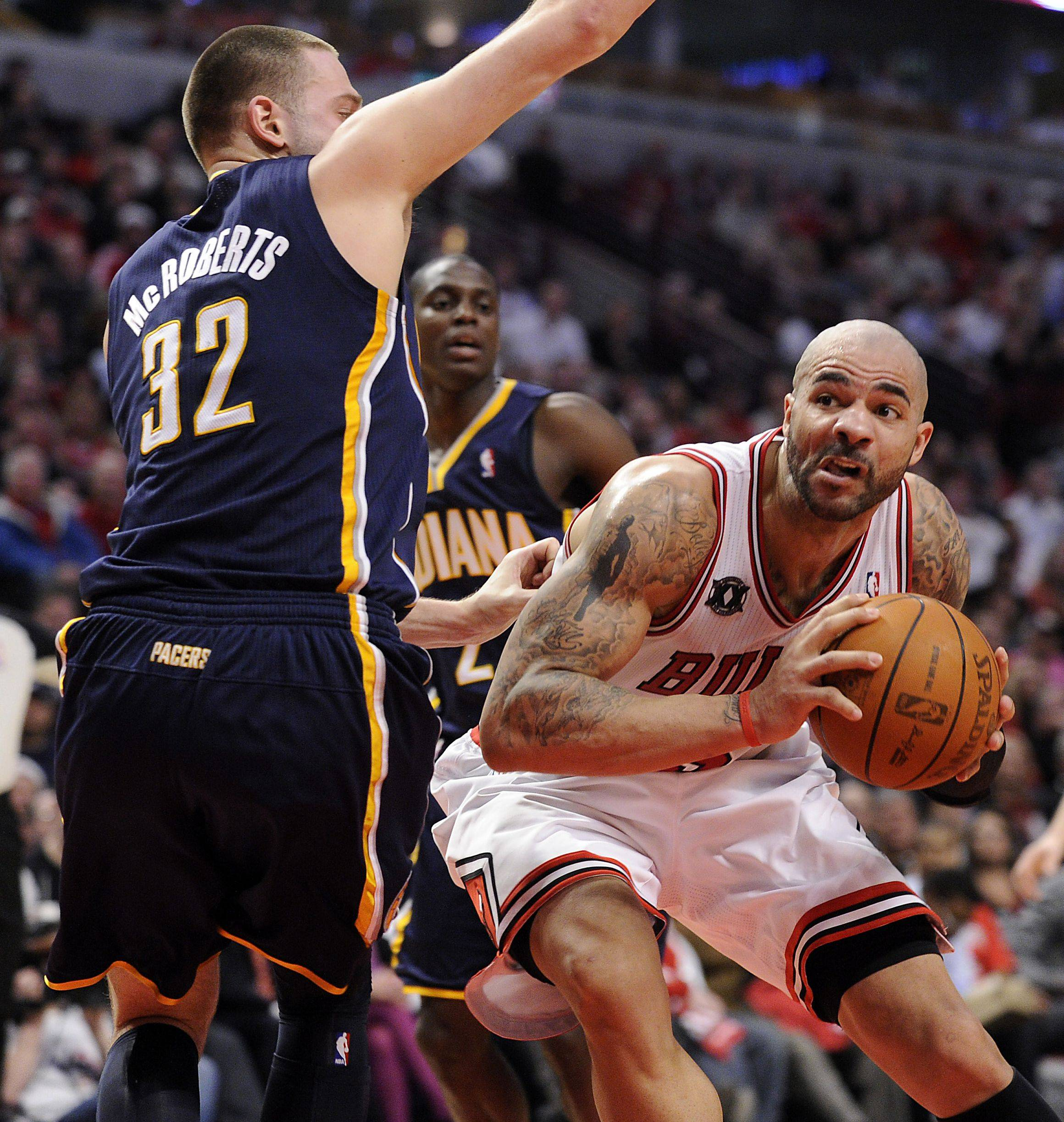 Carlos Boozer works his way around Josh McRoberts in the second quarter of Game 2 of their Eastern Conference playoff series Monday at the United Center.