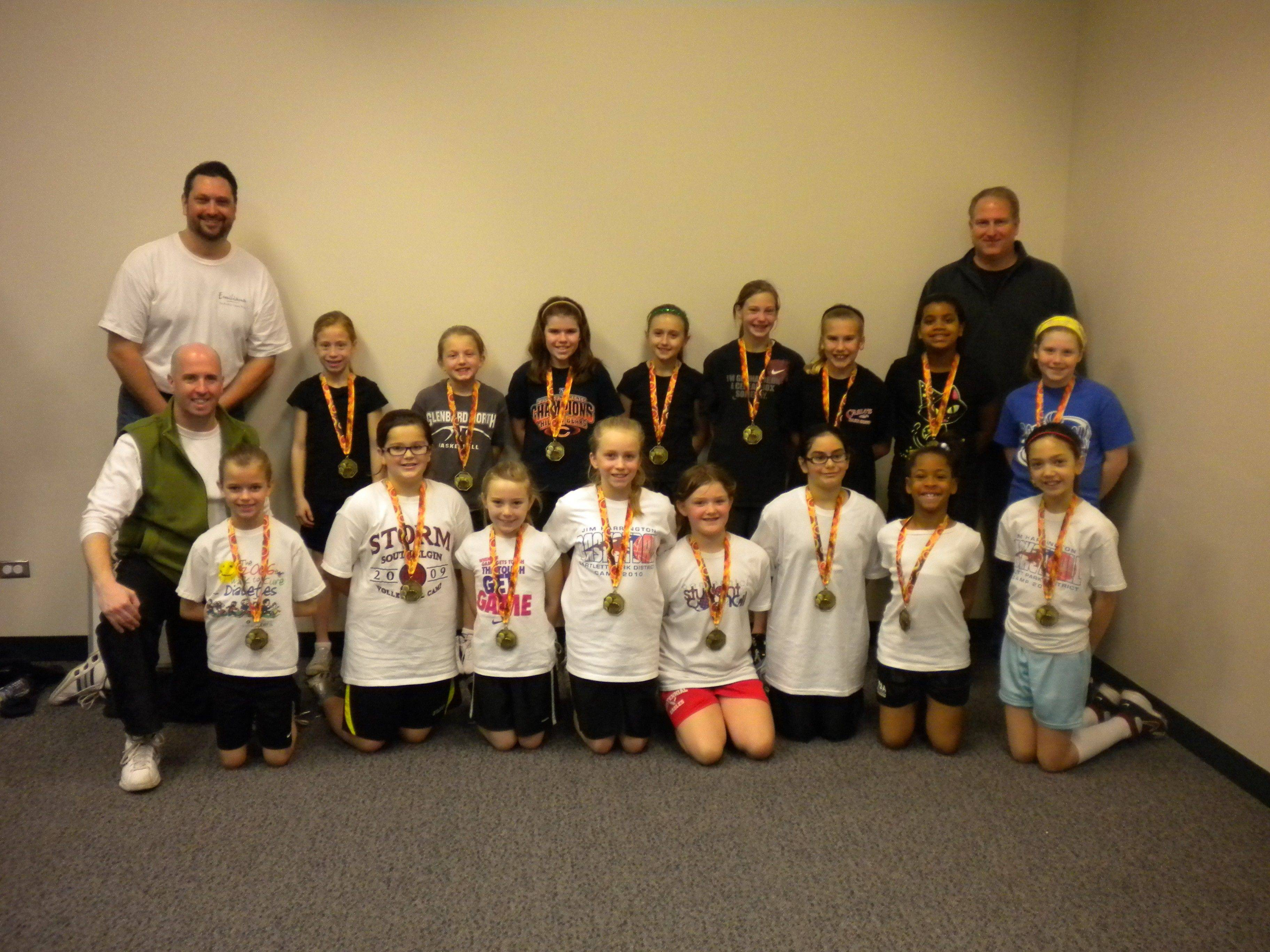 Third/fourth-grade team, from left, are front row wearing white: Maddie Sharko, Megan McClure, Ashley Sullivan, Analise Richcreek, Kailey Halterman, Brooke Cambra, Aryanna Williams and Savannah Standefer; Back row wearing black: Coach John Standefer, Kaleigh Canavan, Hannah Walker, Megan Lombardo, Anna Tomillo, Paige Edmier, Teagan Noesen, Camille Luckett and Julia Wafford; standing behind left side, Coach Jason Sharko; right side: Coach John Wafford.