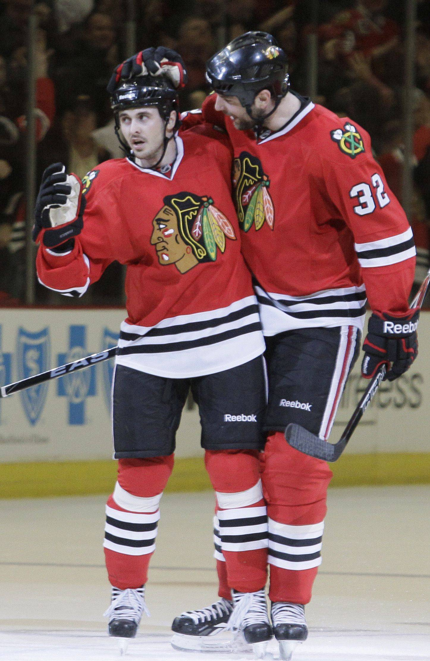 Chicago Blackhawks center Dave Bolland, left, celebrates his second-period goal with defenseman John Scott (32) .