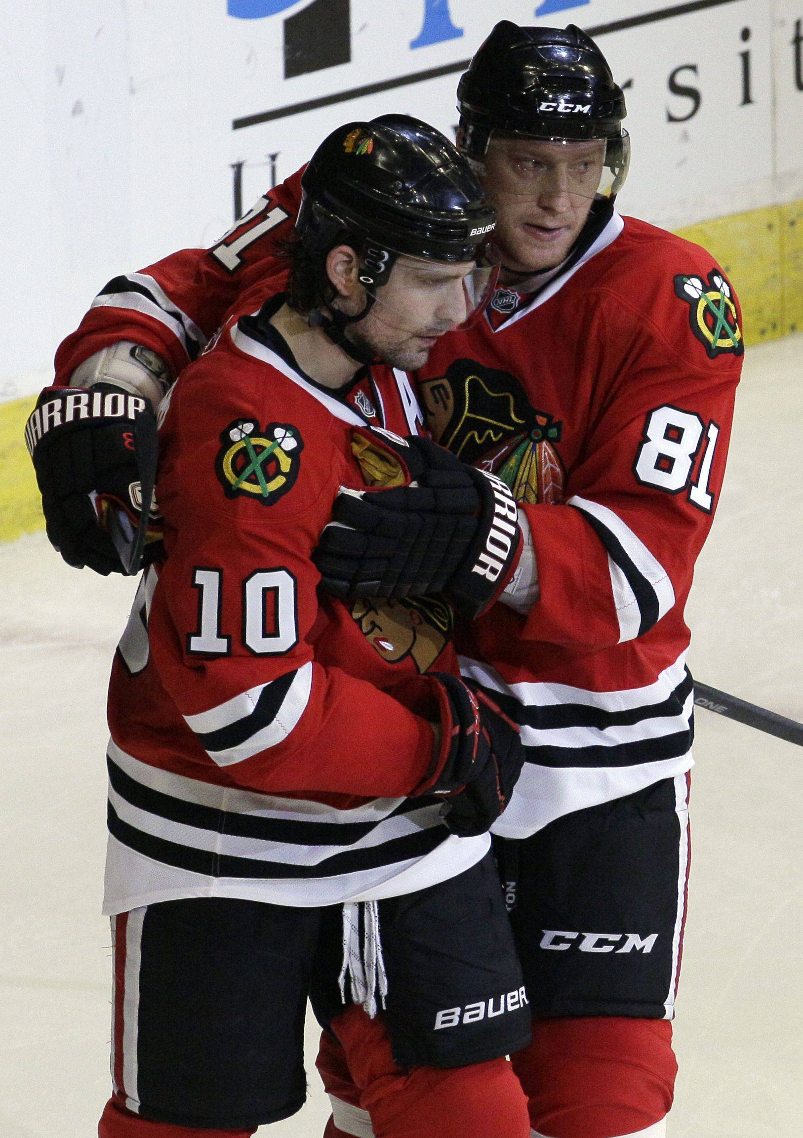 Chicago Blackhawks center Patrick Sharp (10) celebrates his third-period goal with right wing Marian Hossa (81) .