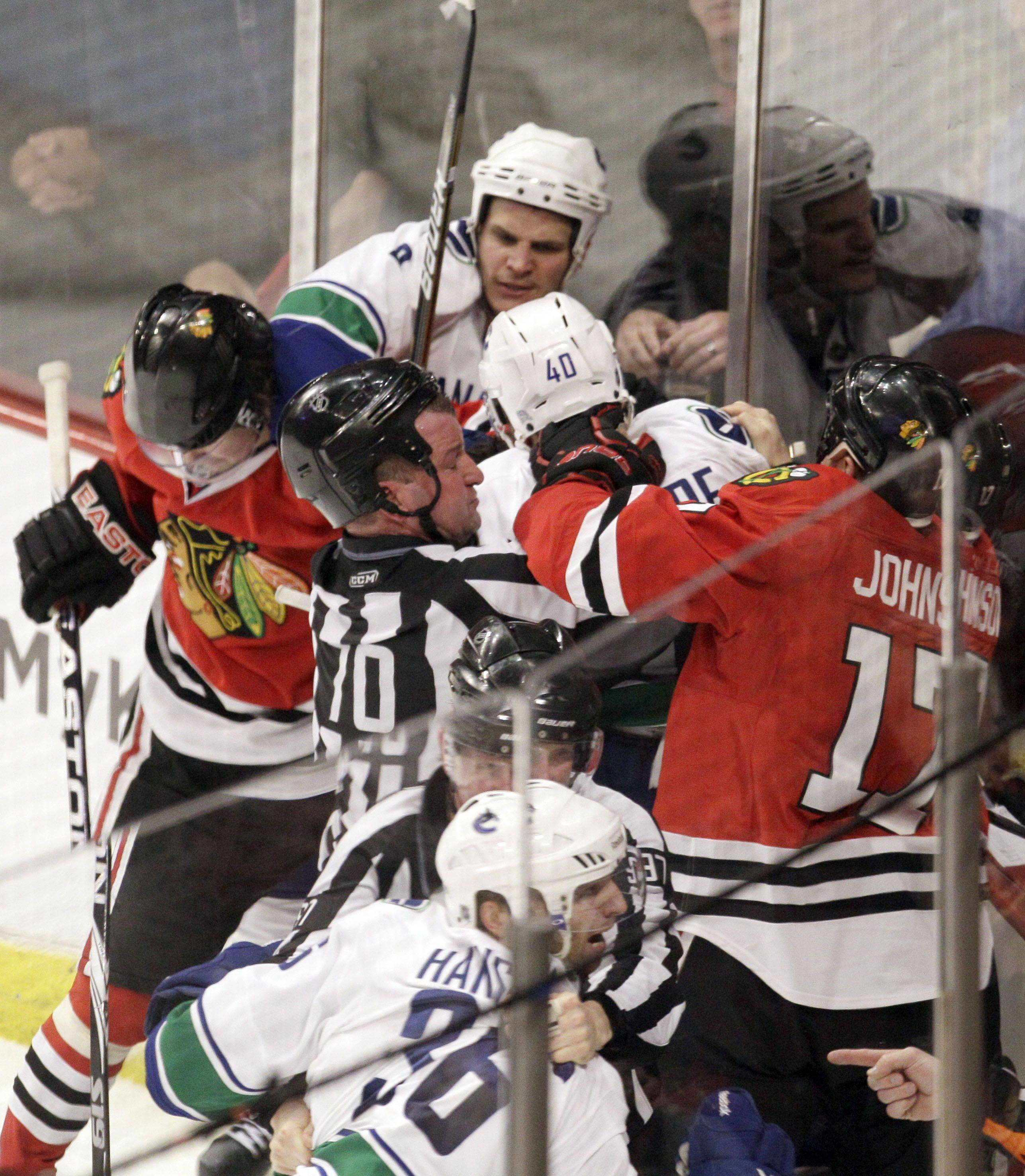 Officials break up a fight during the third period.