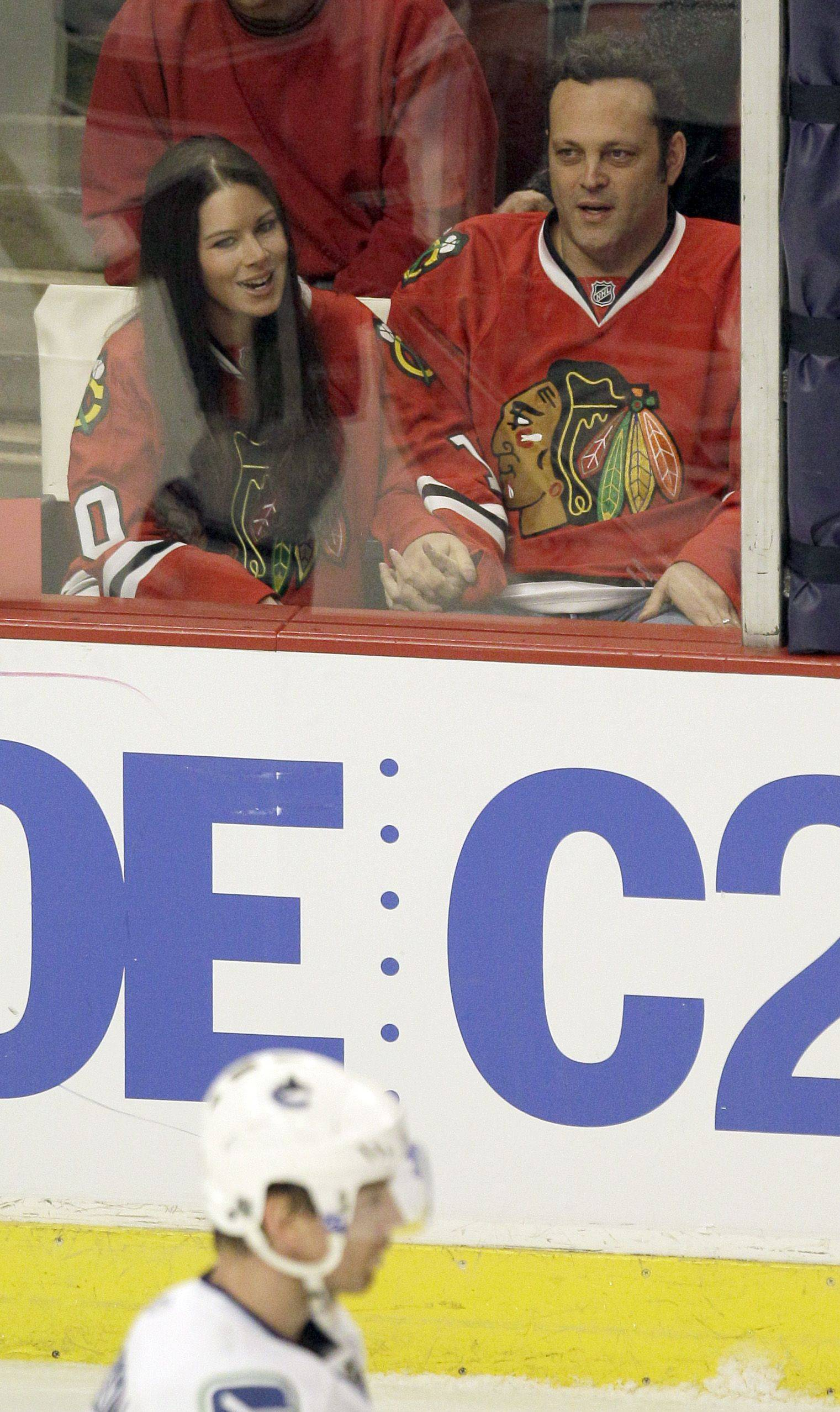 Actor Vince Vaughn, right, sits with his wife, Kyla Weber, during the first period.