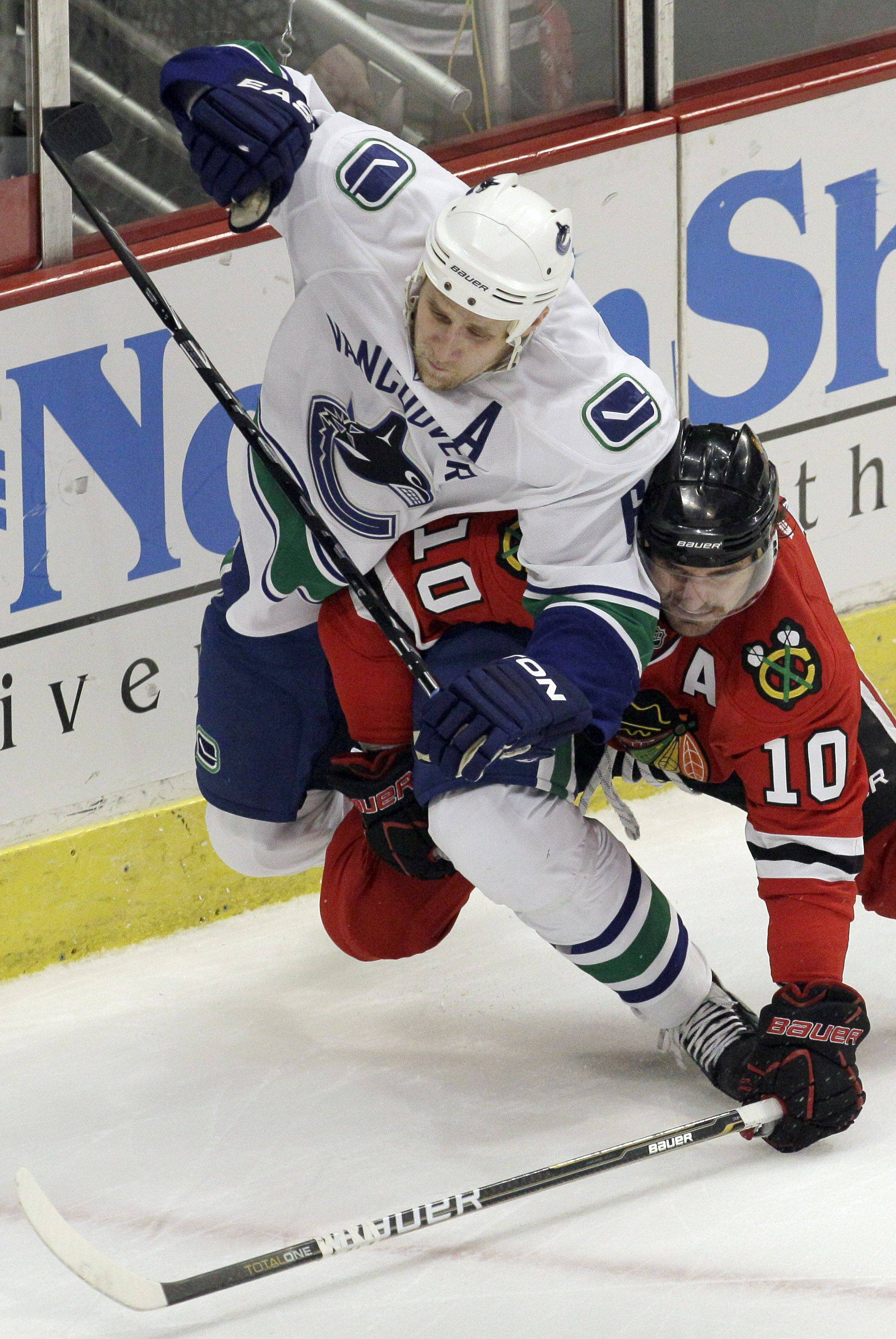 Vancouver Canucks defenseman Sami Salo, left, and Chicago Blackhawks center Patrick Sharp (10) vie for the puck during the first period.
