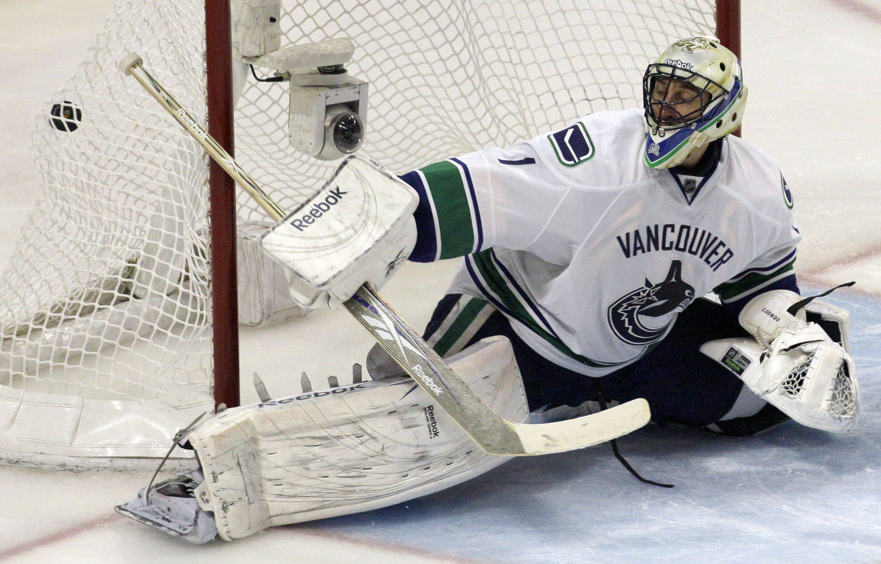 Vancouver Canucks goalie Roberto Luongo is unable to make the save on a shot by Chicago Blackhawks center Patrick Sharp.