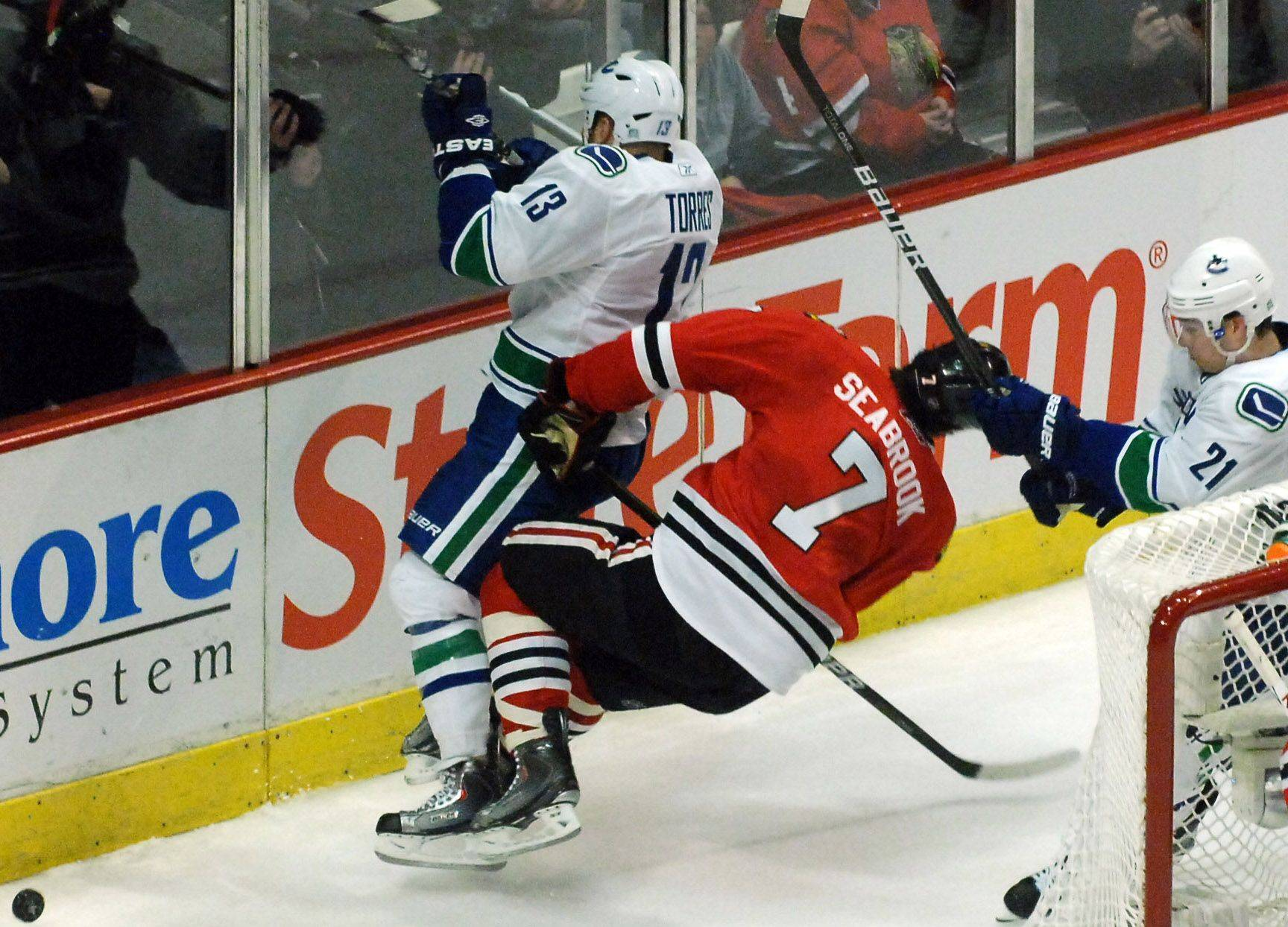 This hit on Brent Seabrook by Vancouver's Raffi Torres (13) earned the Canucks' left winger only a two-minute penalty in Game 3 of the NHL Western Conference quarterfinals Sunday, but it has knocked Seabrook out for Game 4 at the United Center tonight.
