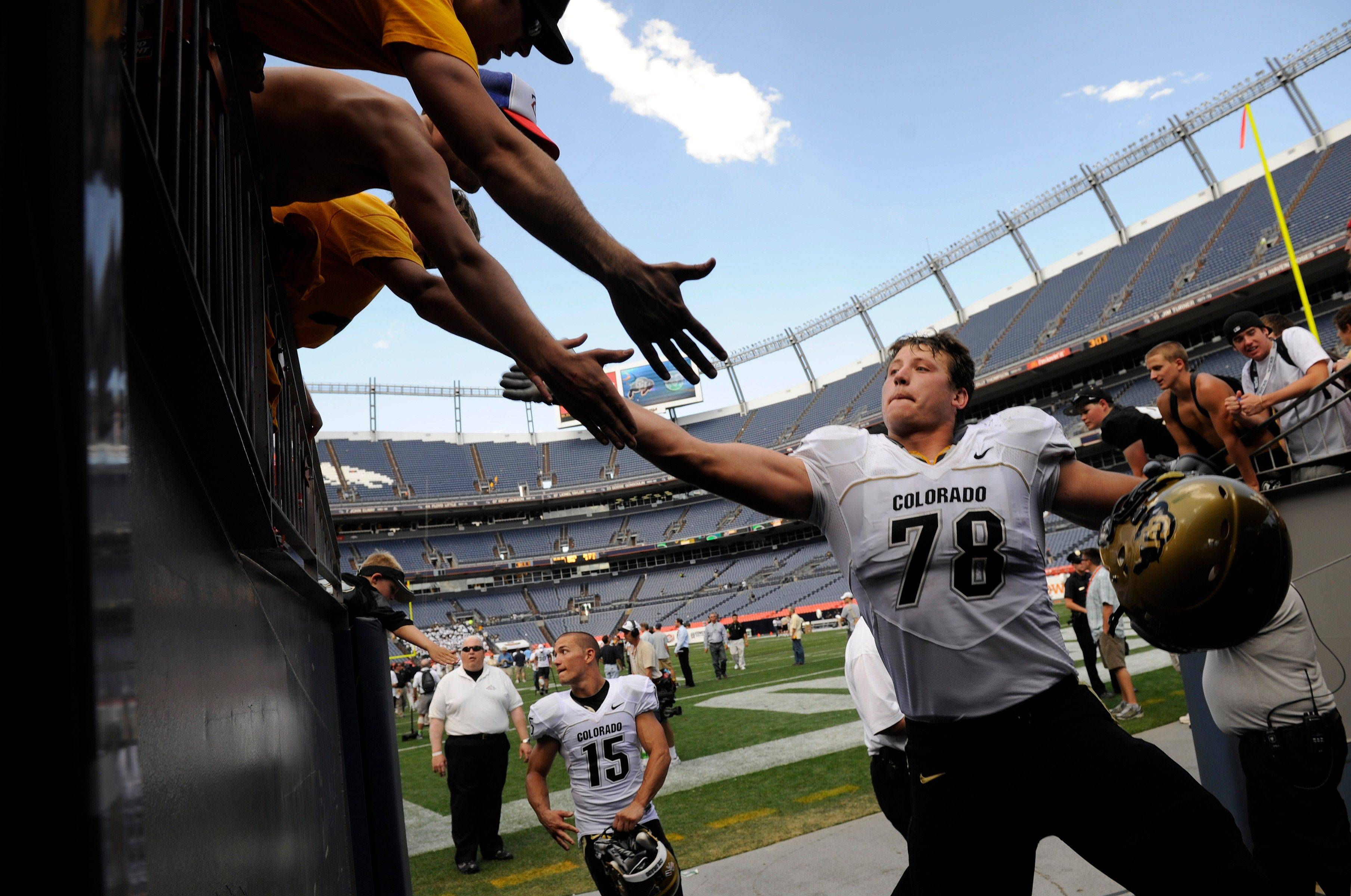 Colorado's Nate Solder, right, gives high-fives to fans after the Buffaloes defeated Colorado State 24-3 in a NCAA college football game at Invesco Field in Denver on Saturday, Sept. 4, 2010.