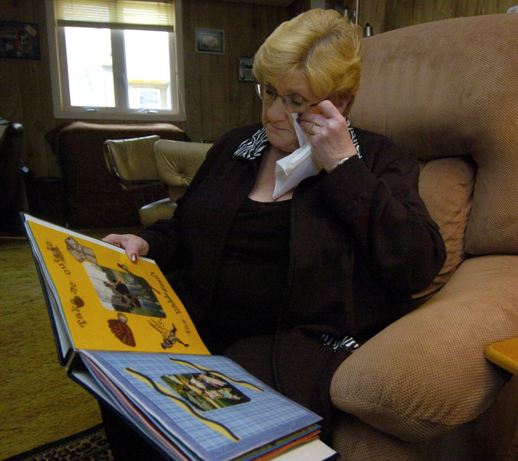 Nanci Koschman of Mount Prospect wipes away tears while viewing scrapbook photos of her son, David.