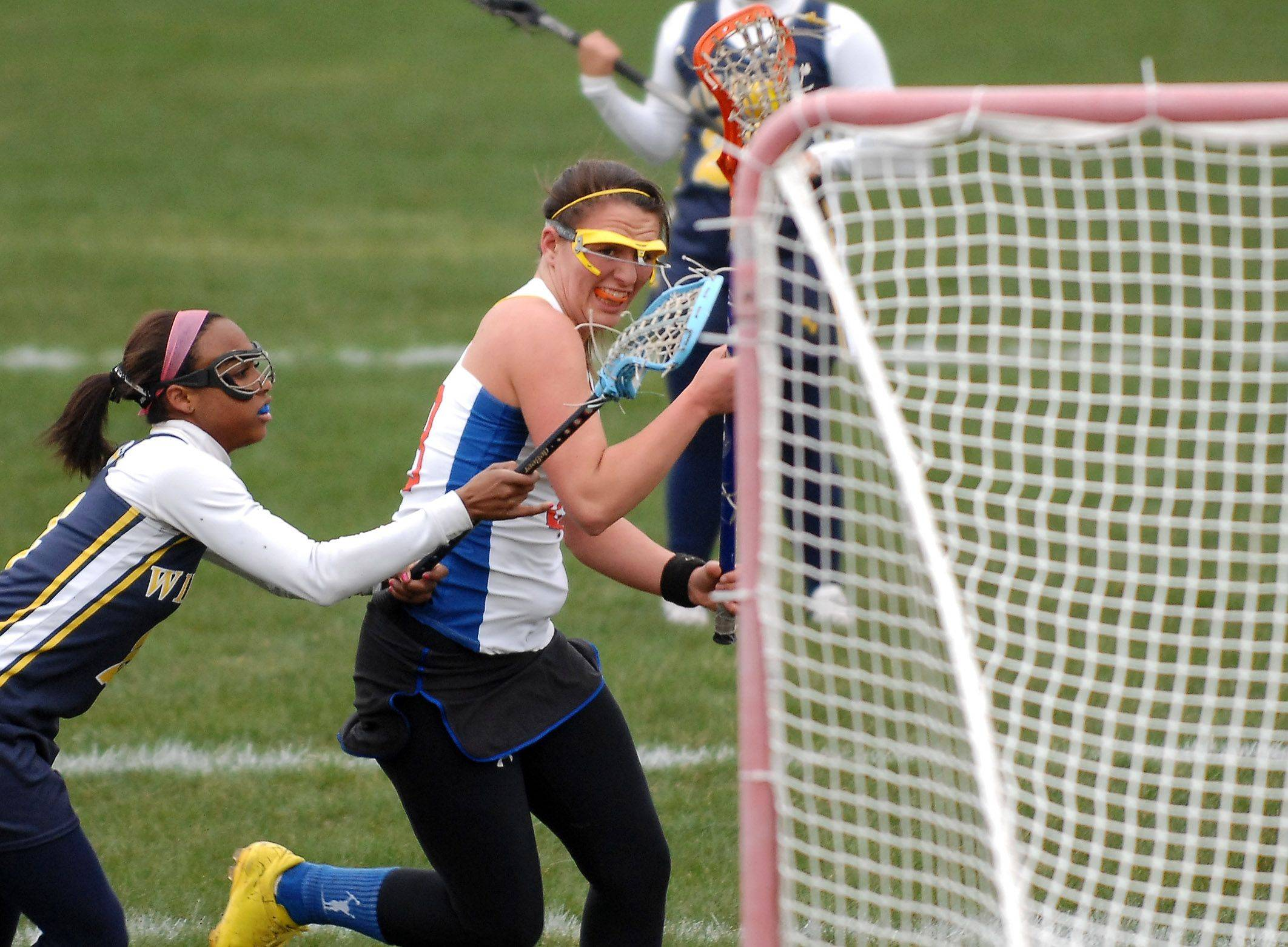 Katie Bogle of the St. Charles Co-op battles past Neuqua Valley's Taylor Maduro before she shoots and scores during girls lacrosse action in St. Charles Thursday, April 21, 2011.