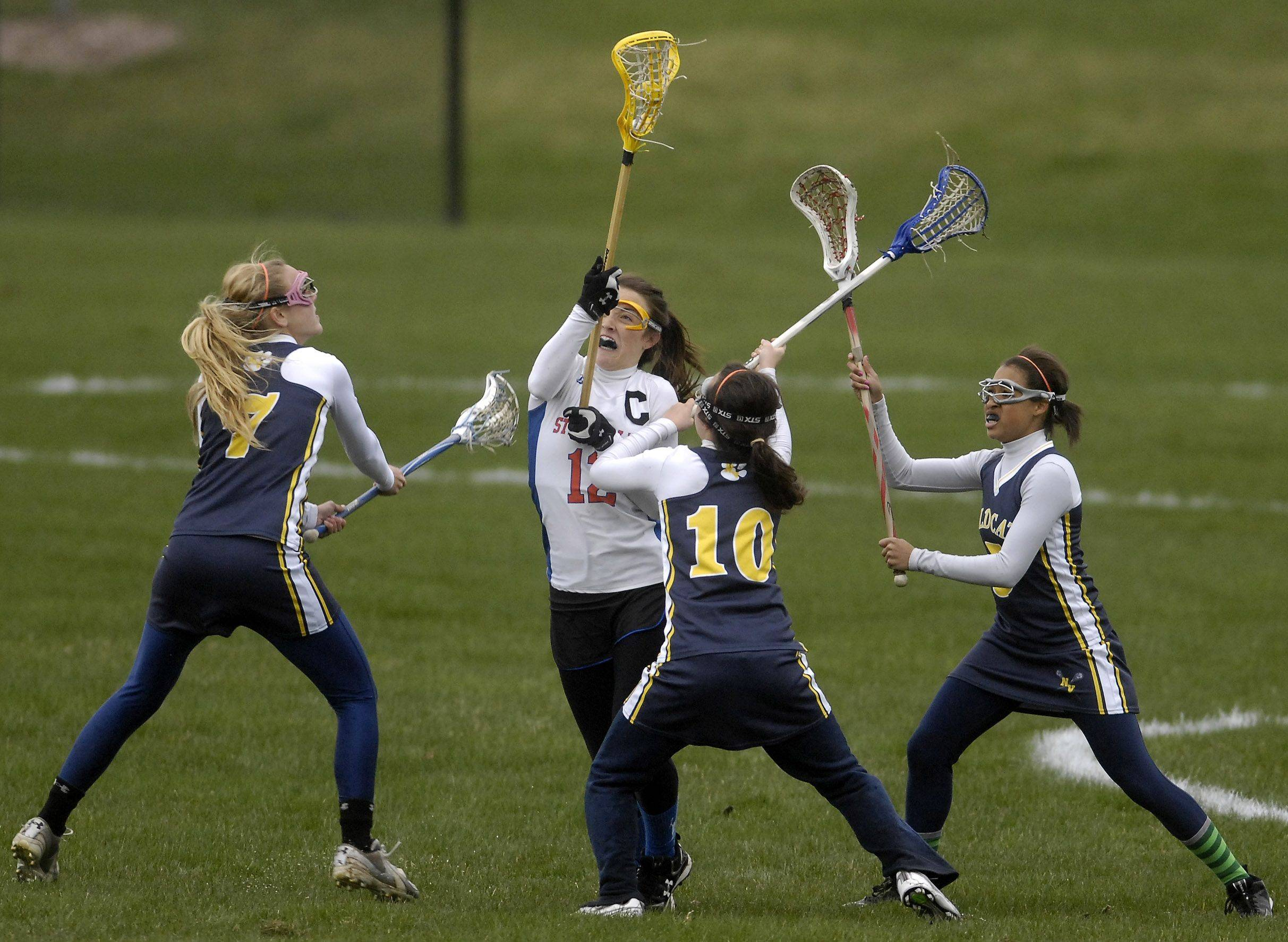 Meghan Brady of the St. Charles Co-op team slices through a trio of Neuqua Valley defenders during girls lacrosse action in St. Charles Thursday, April 21, 2011.