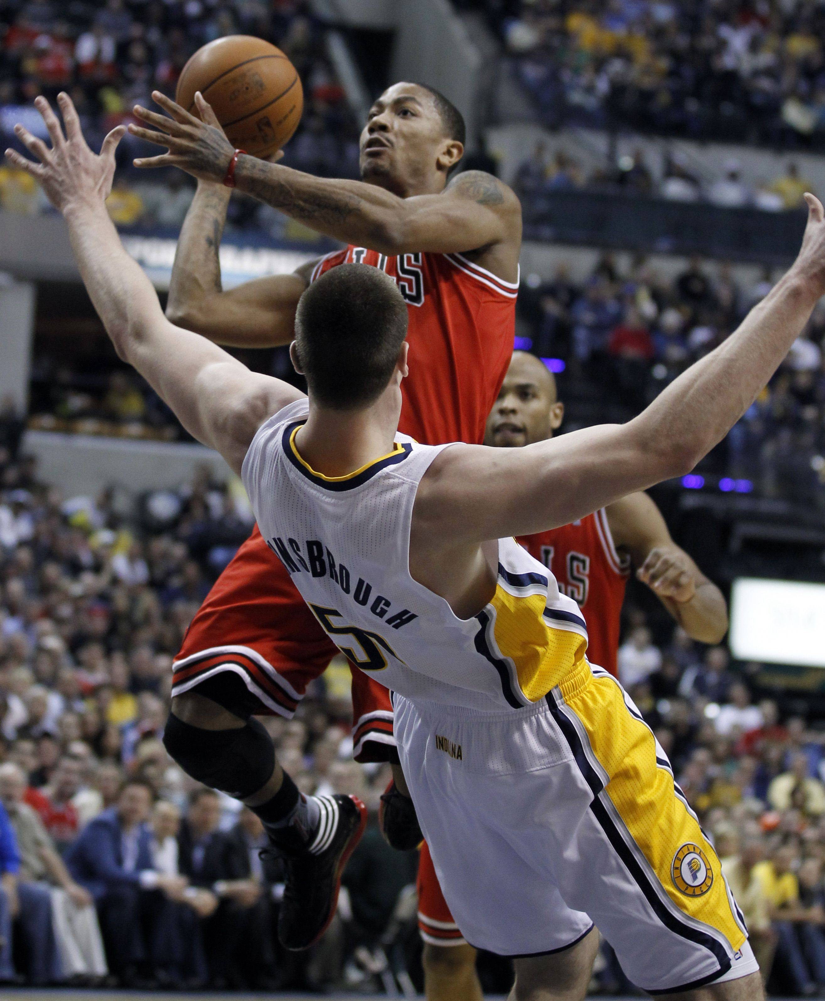Indiana Pacers' Tyler Hansbrough (50) tries to draw a charging foul as Chicago Bulls' Derrick Rose drives to the basket during the first half.