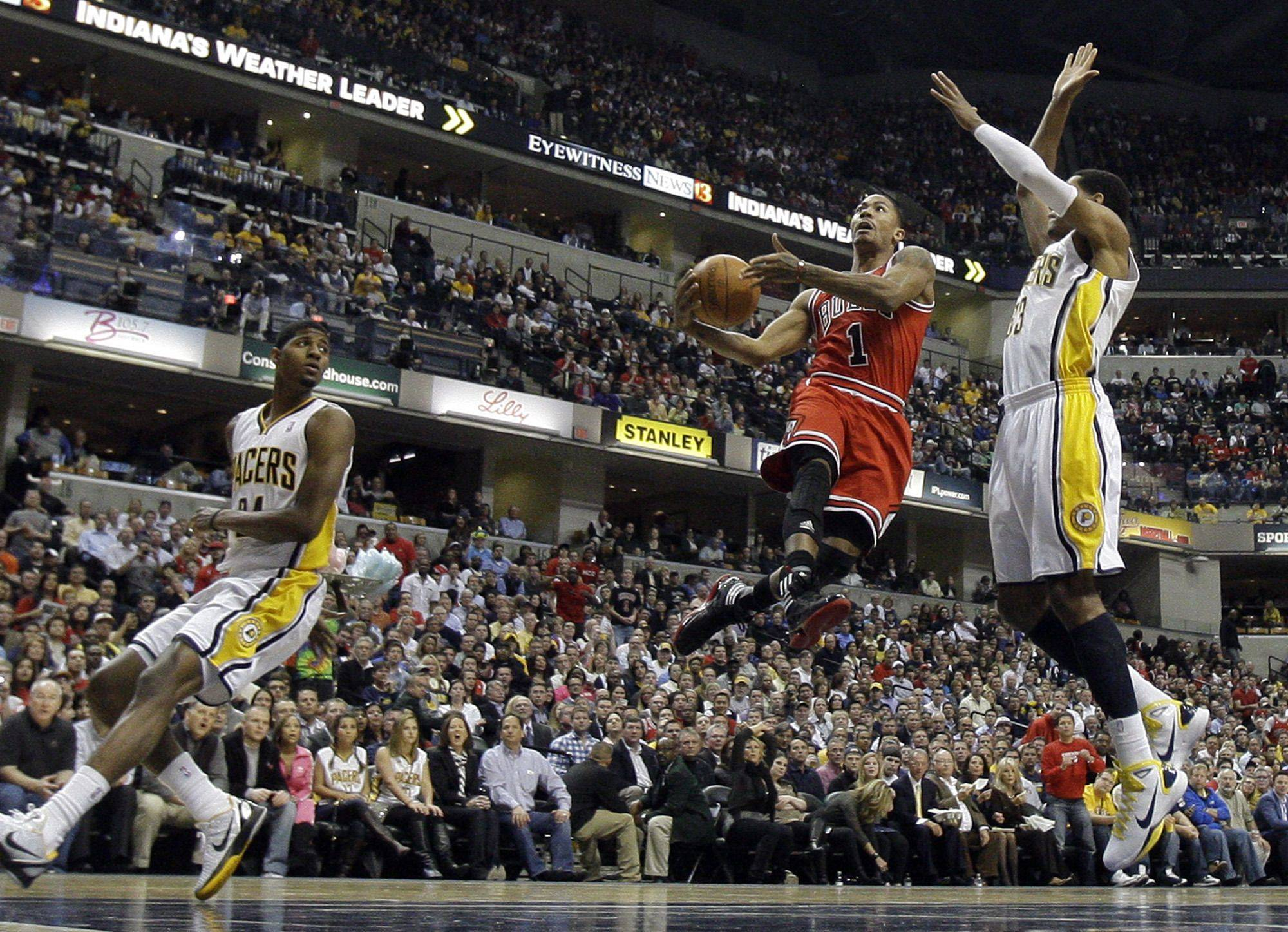 Chicago Bulls' Derrick Rose (1) goes up for a shot between Indiana Pacers' Danny Granger (33) and Paul George (24) during the first half.
