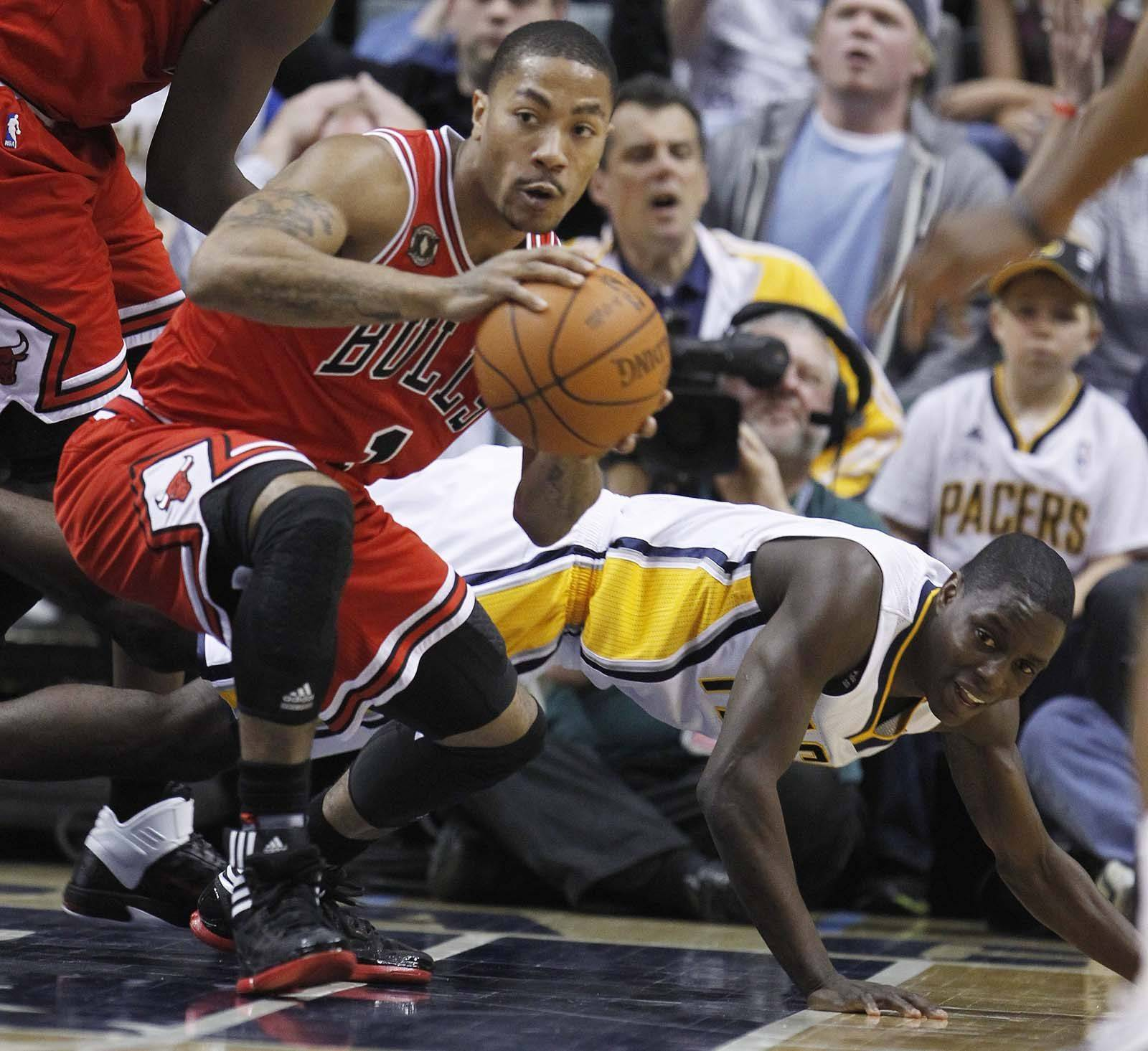 Chicago Bulls' Derrick Rose (1) grabs a loose ball in front of Indiana Pacers' Darren Collison during the first half.