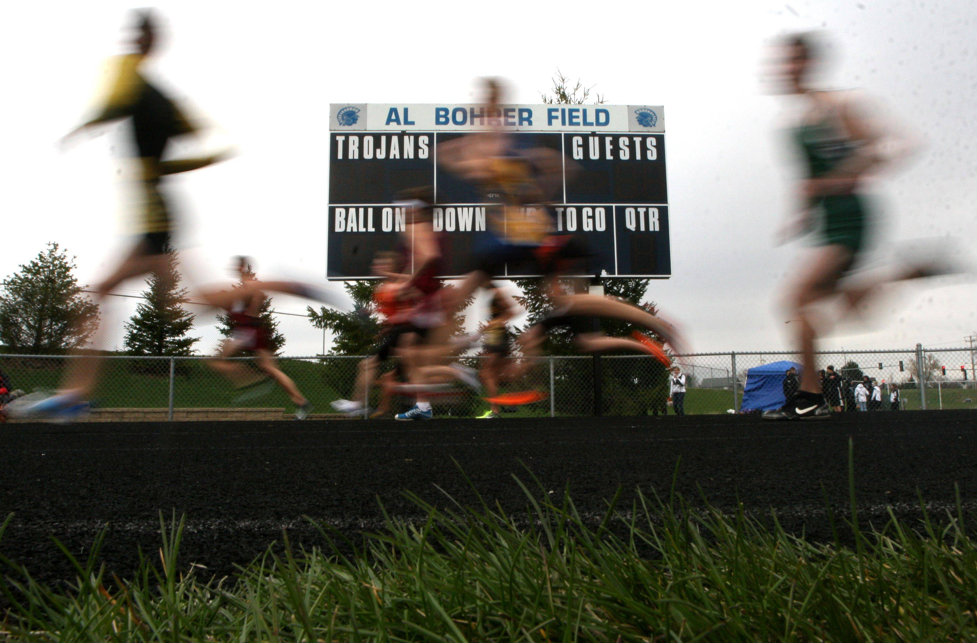 Boys competitors take part in the 3200-meter run during the McHenry County Track Meet at Al Bohrer Field on the campus of Cary-Grove High School Thursday evening.